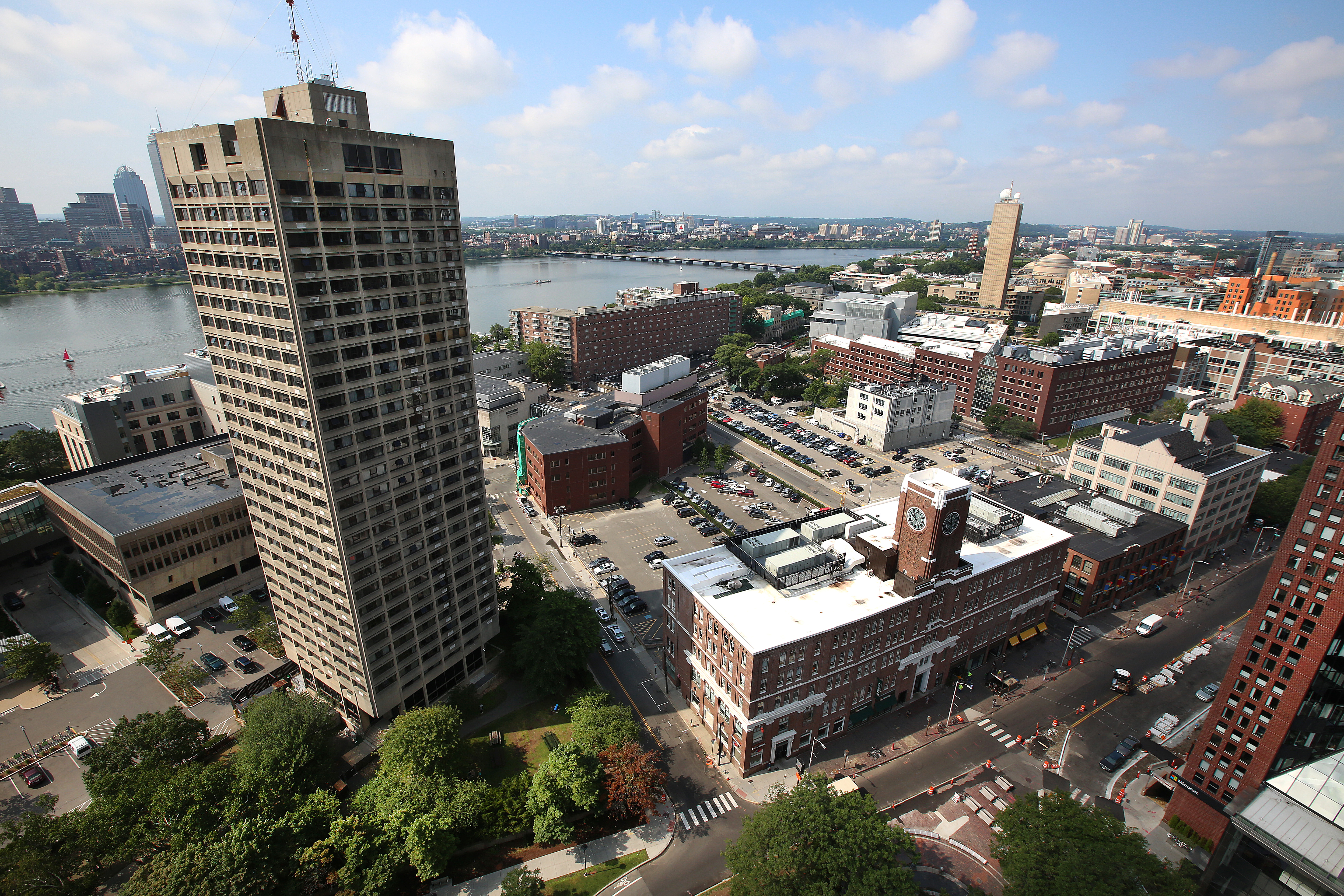 An aerial view of an urban streetscape next to a river, and there's one tall tower.