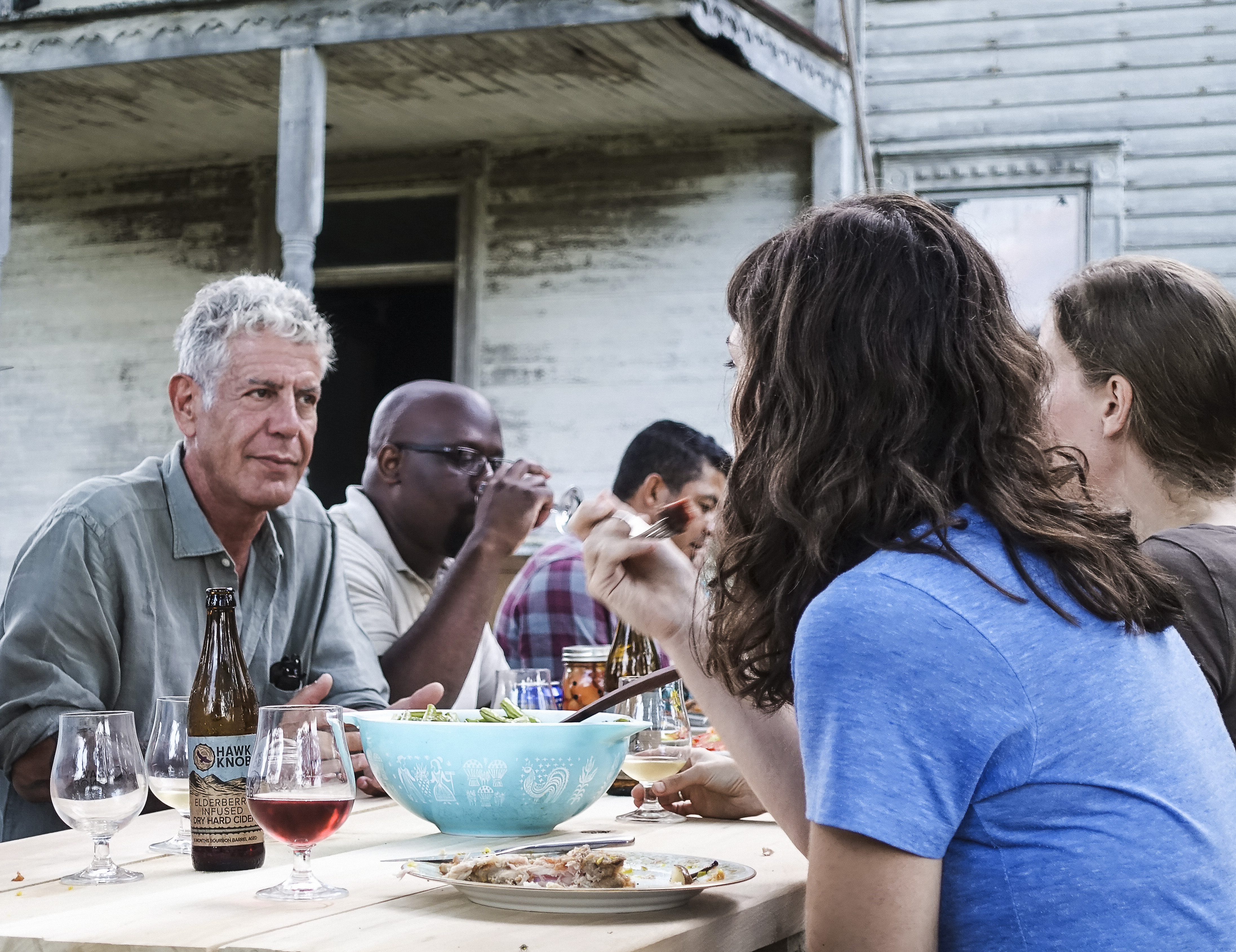 Anthony Bourdain sitting at an outdoor table in a scene from Parts Unknown: West Virginia.