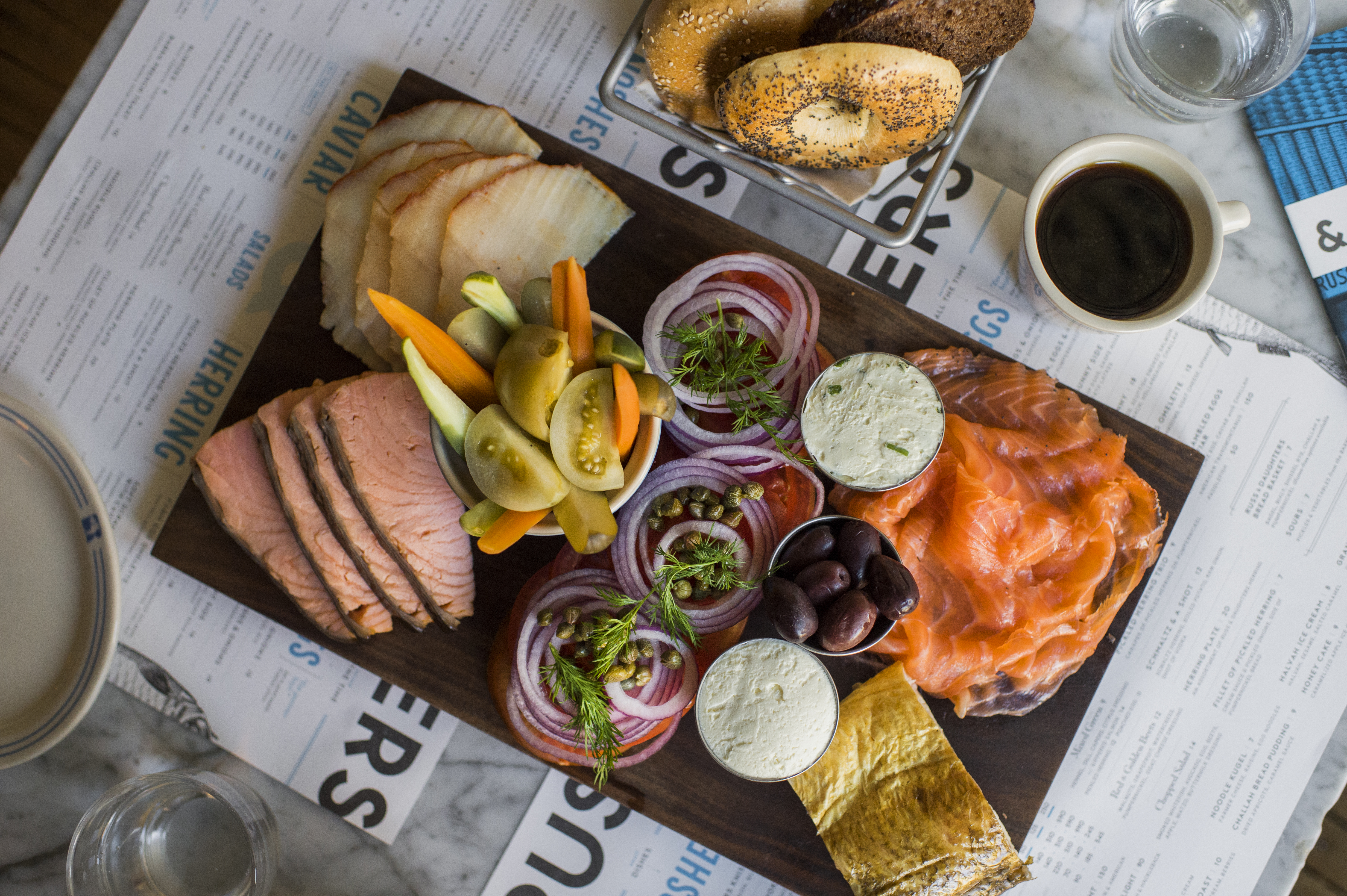 A wooden board covered in smoked fish, cream cheese, and pickled vegetables