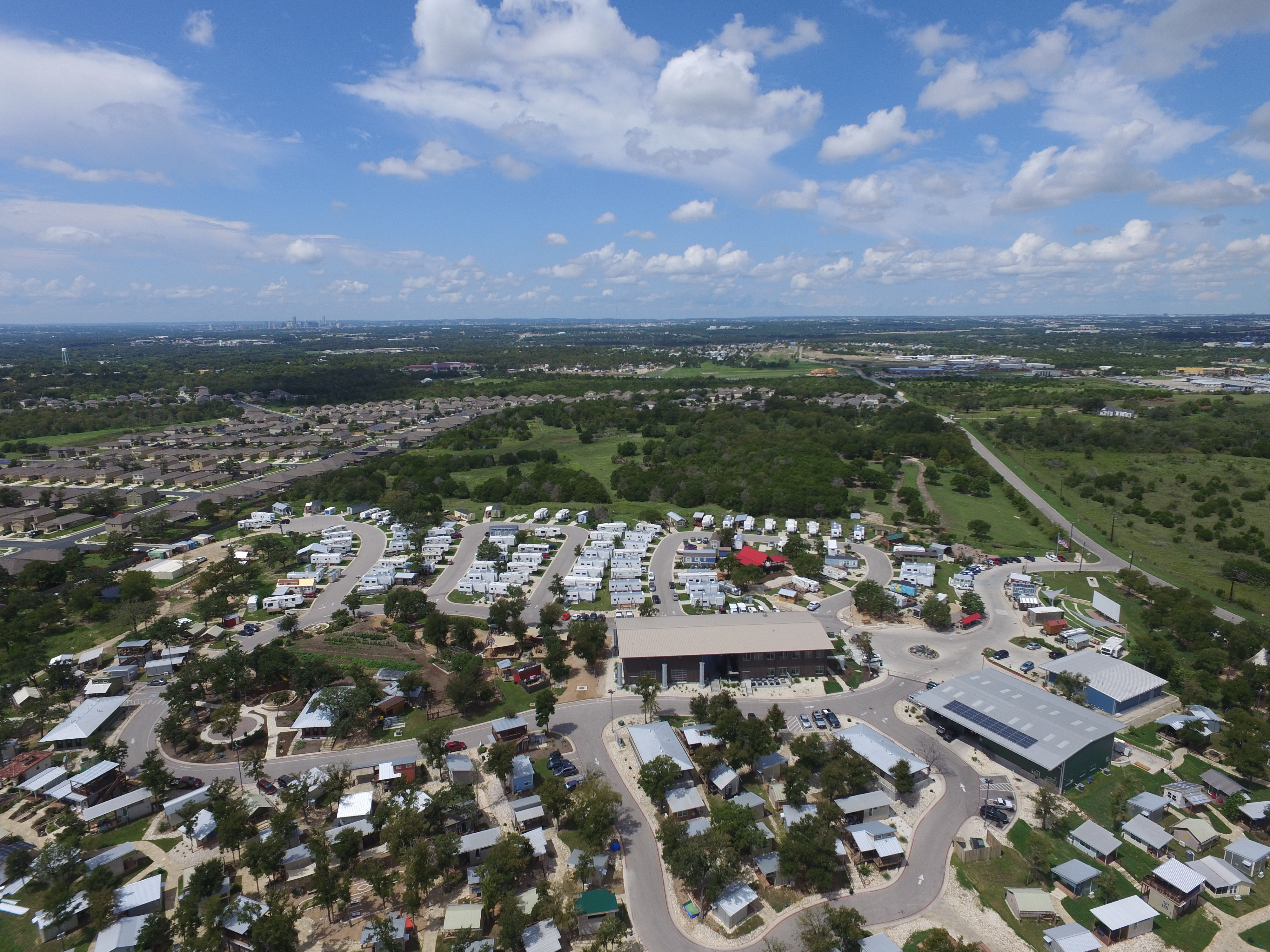 Aerial view of small development with tiny homes, RVs, community buildings, and adjacent land