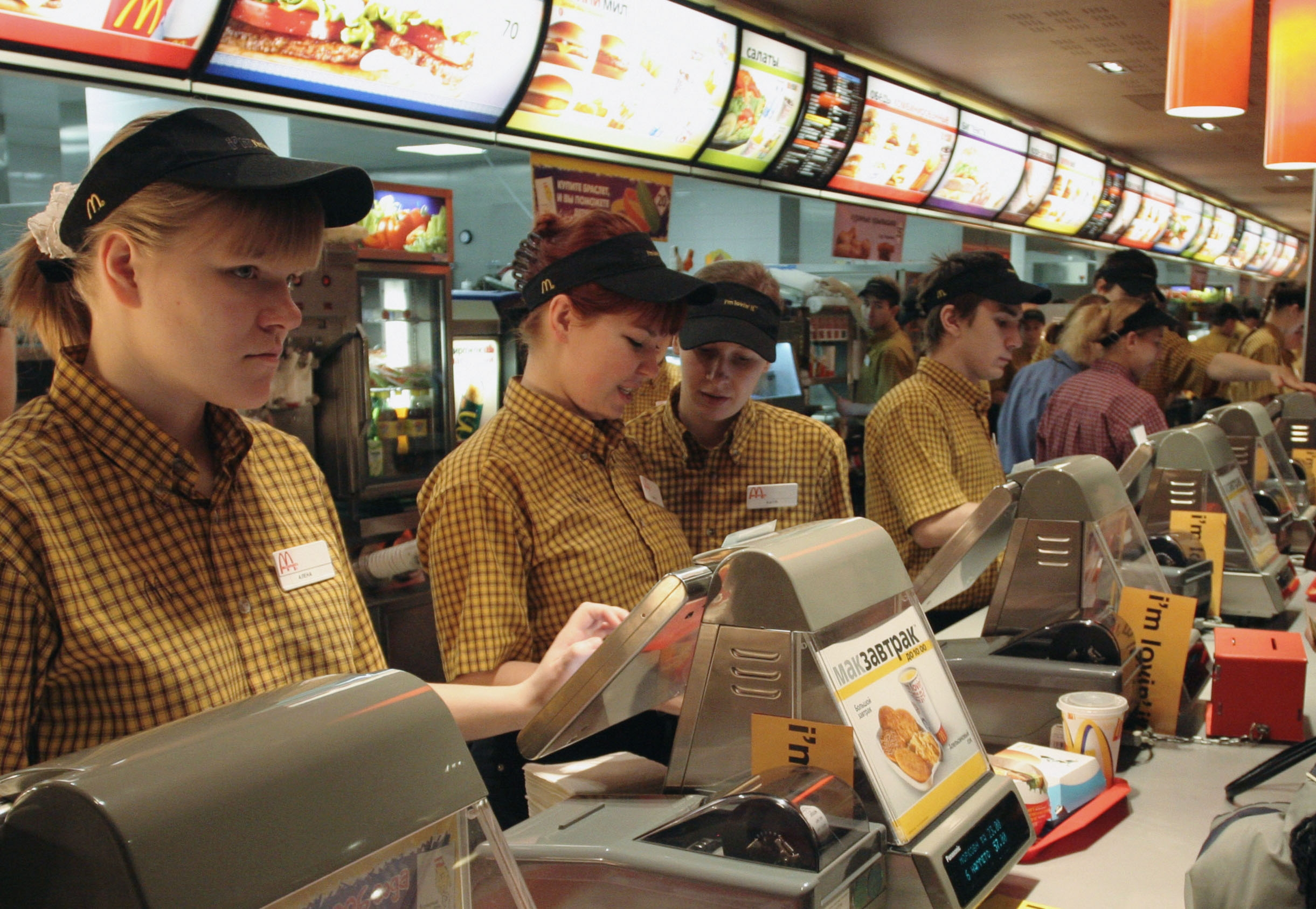 Cashiers standing behind a counter at a McDonald's