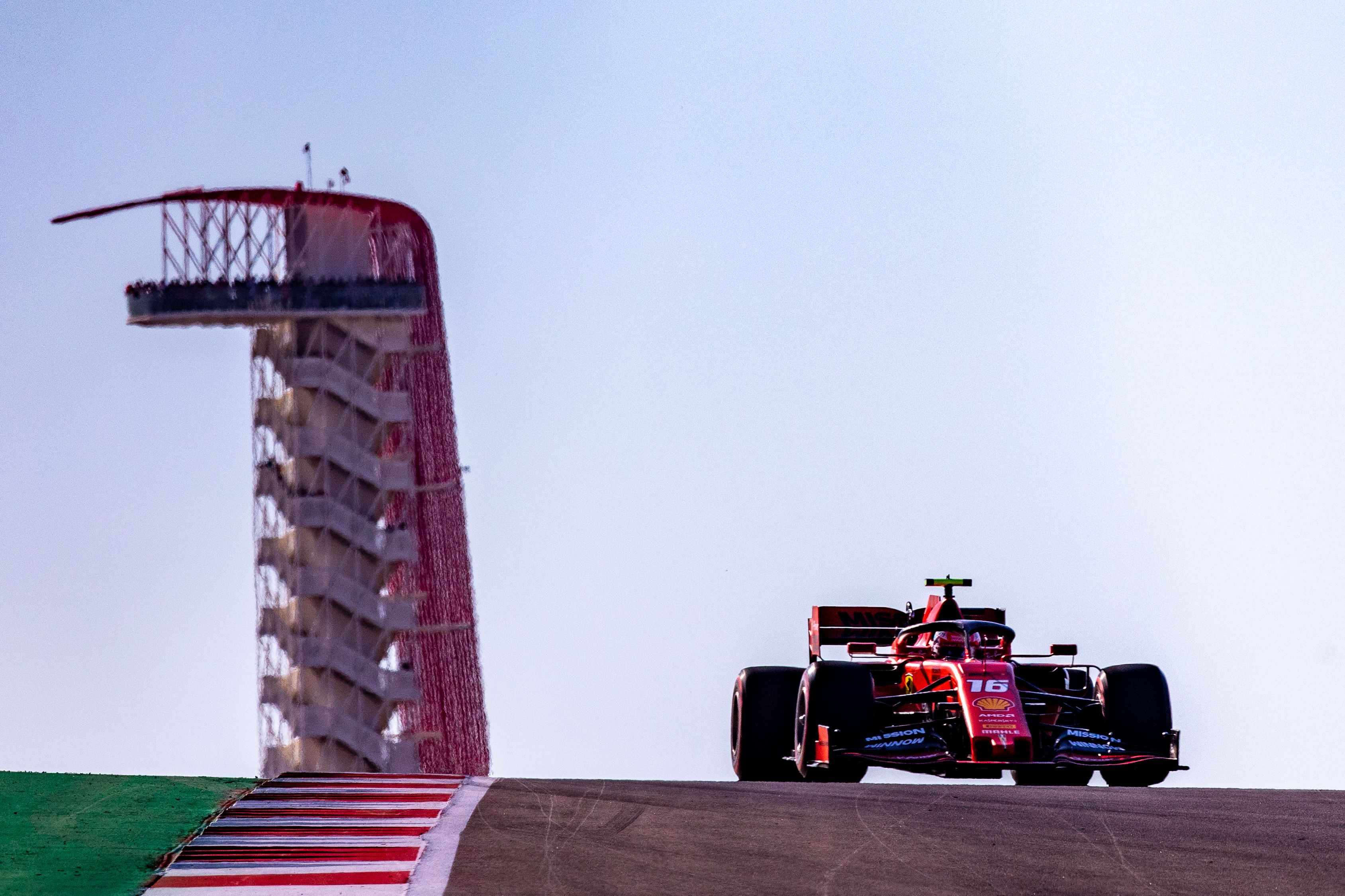 A red race car next to a tall structure in the back.