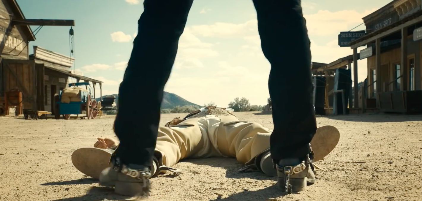 The Ballad of Buster Scruggs - man standing in front of a body lying on the ground