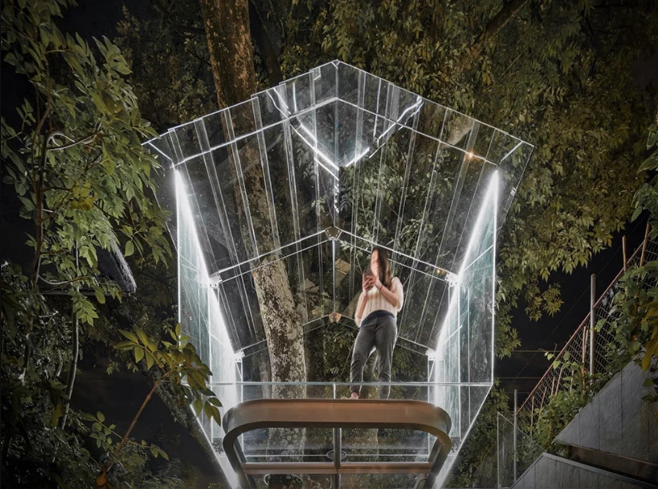Woman in glass treehouse at night
