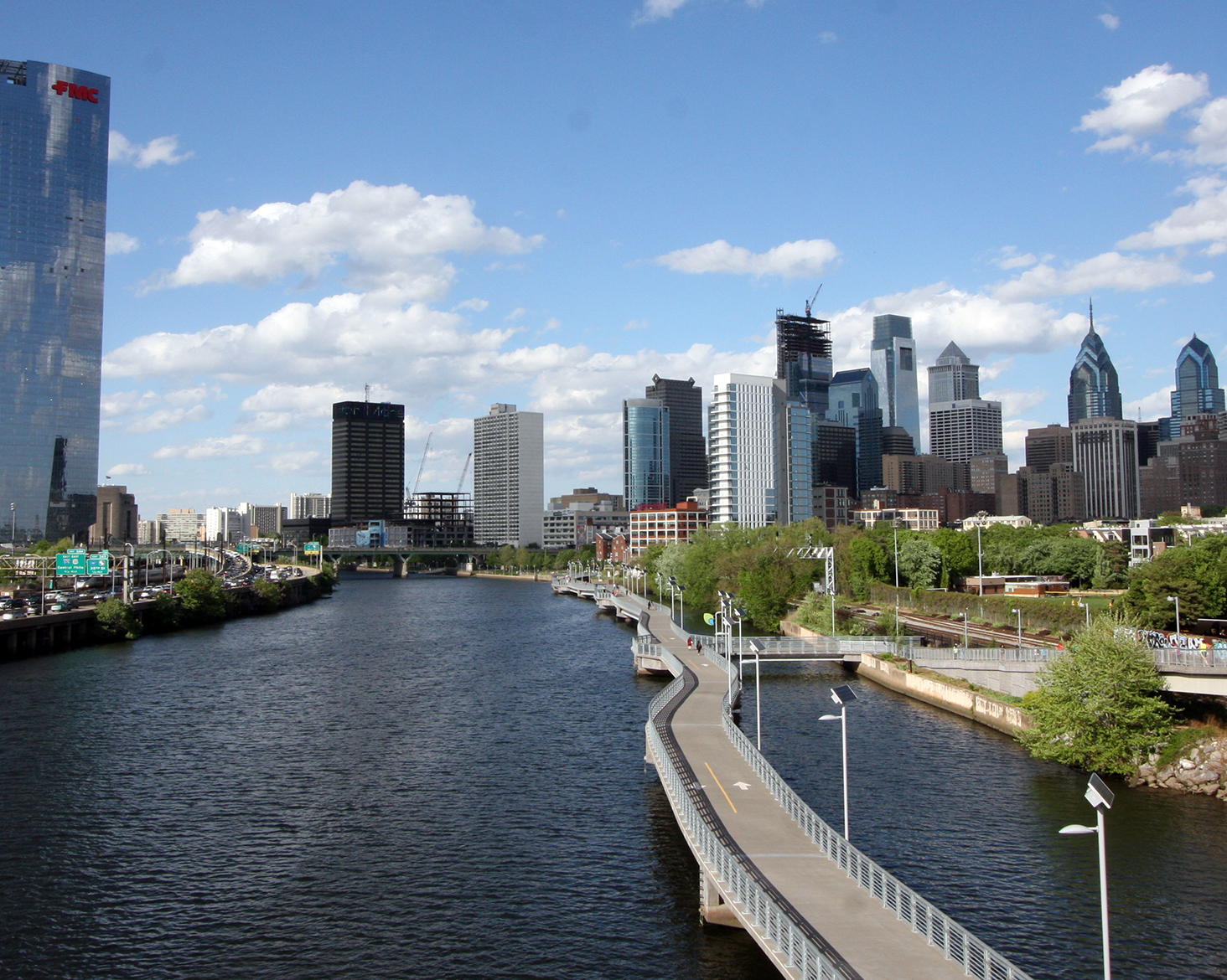 In the foreground is the Schuylkill river with a road spanning over it. In the distance is the Philadelphia skyline