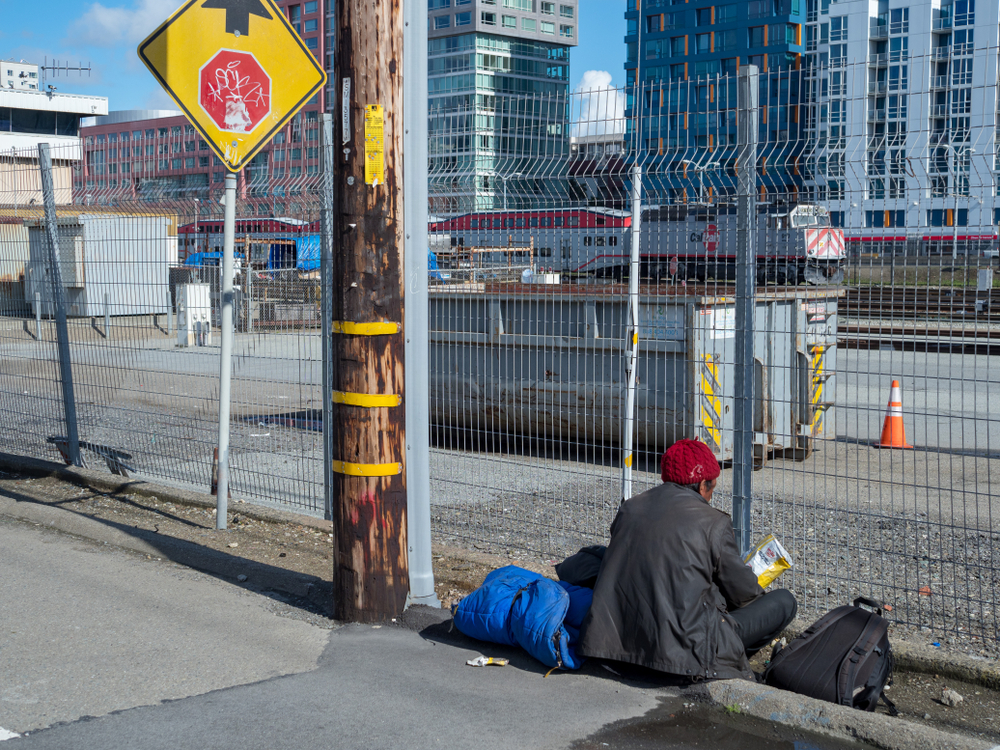 An apparently homeless man sits in front of a cyclone fence, with Muni buses behind it.