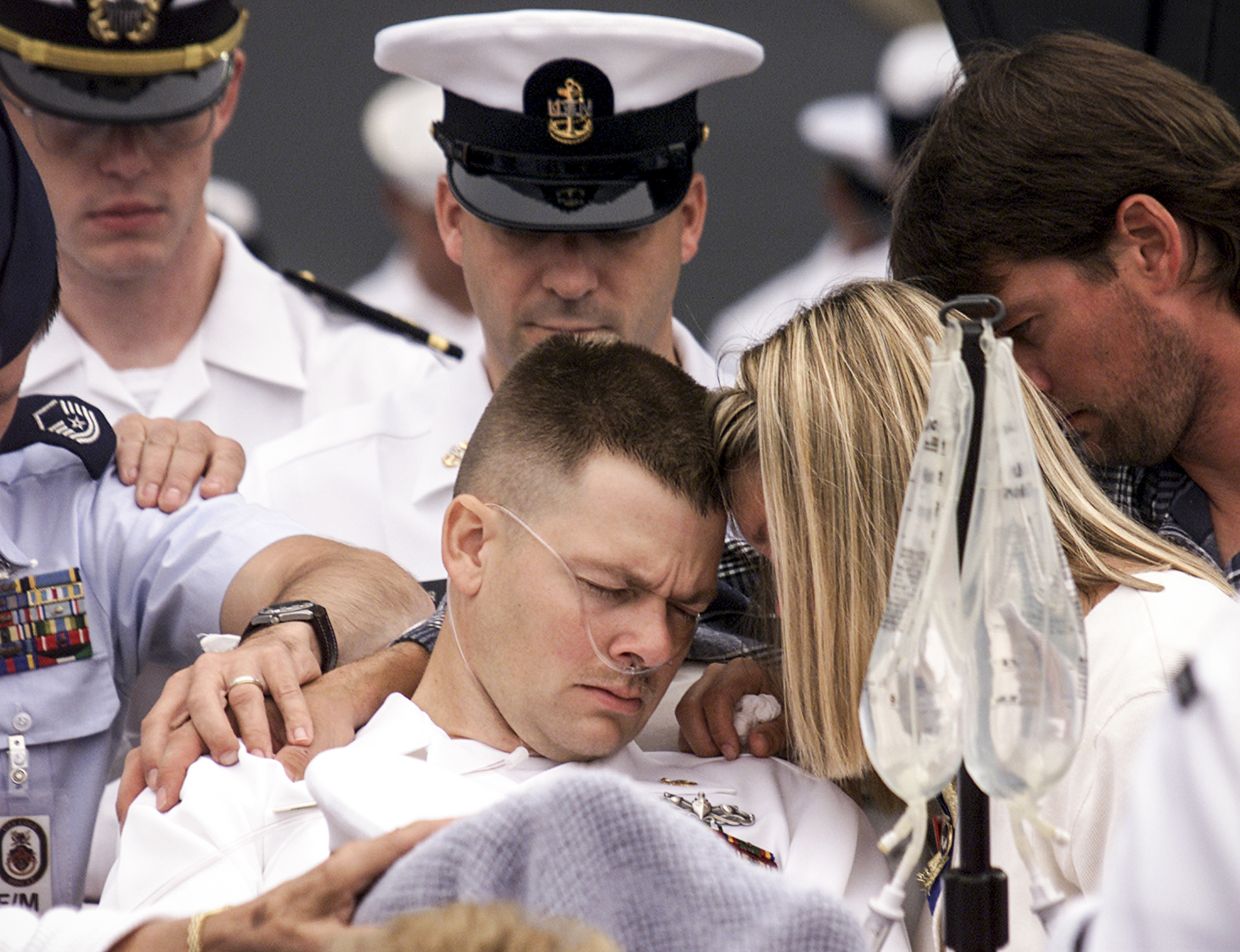 An injured sailor from the USS Cole is comforted by family members during a memorial service attended by President Bill Clinton, in Norfolk, VA, on October 18, 2000.