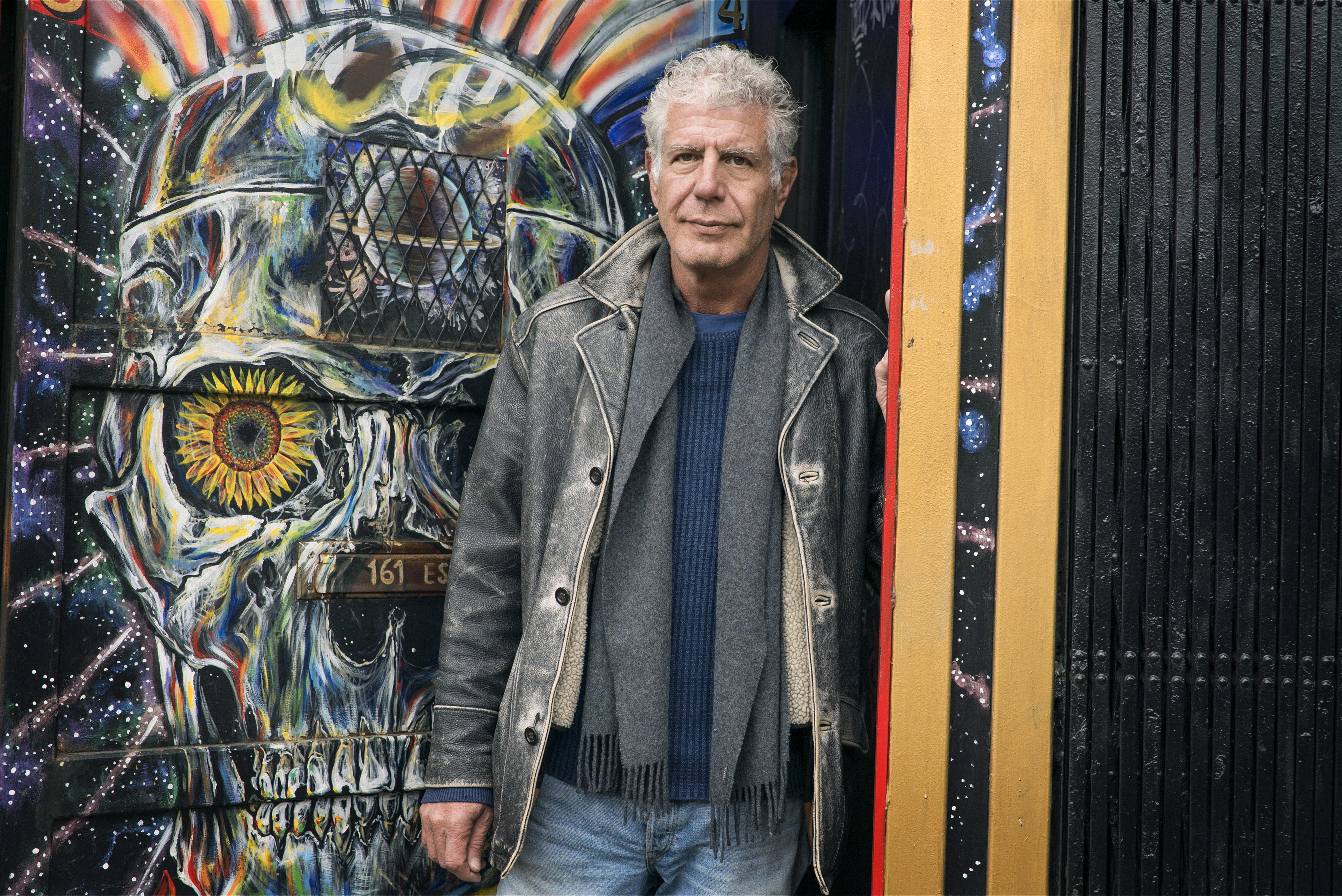 Anthony Bourdain poses with street art outside Patterson's Outlaw Art Gallery in the Lower East Side episode of Parts Unknown.
