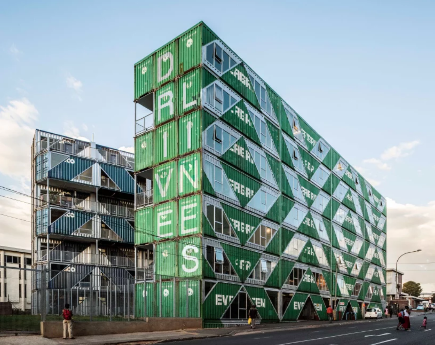 Green shipping container building on busy street