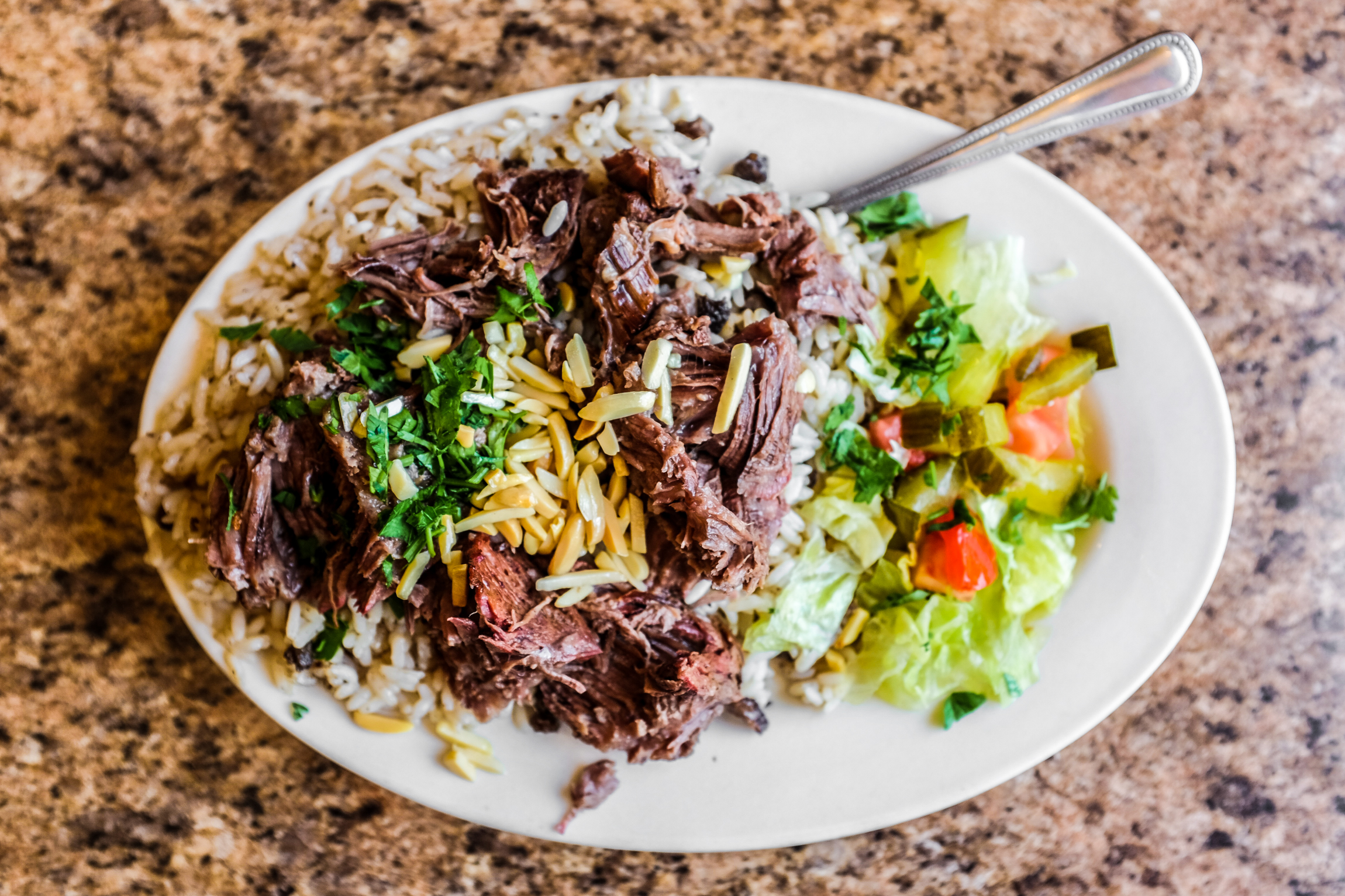 shredded lamb over rice with slivered almonds and a salad on the side