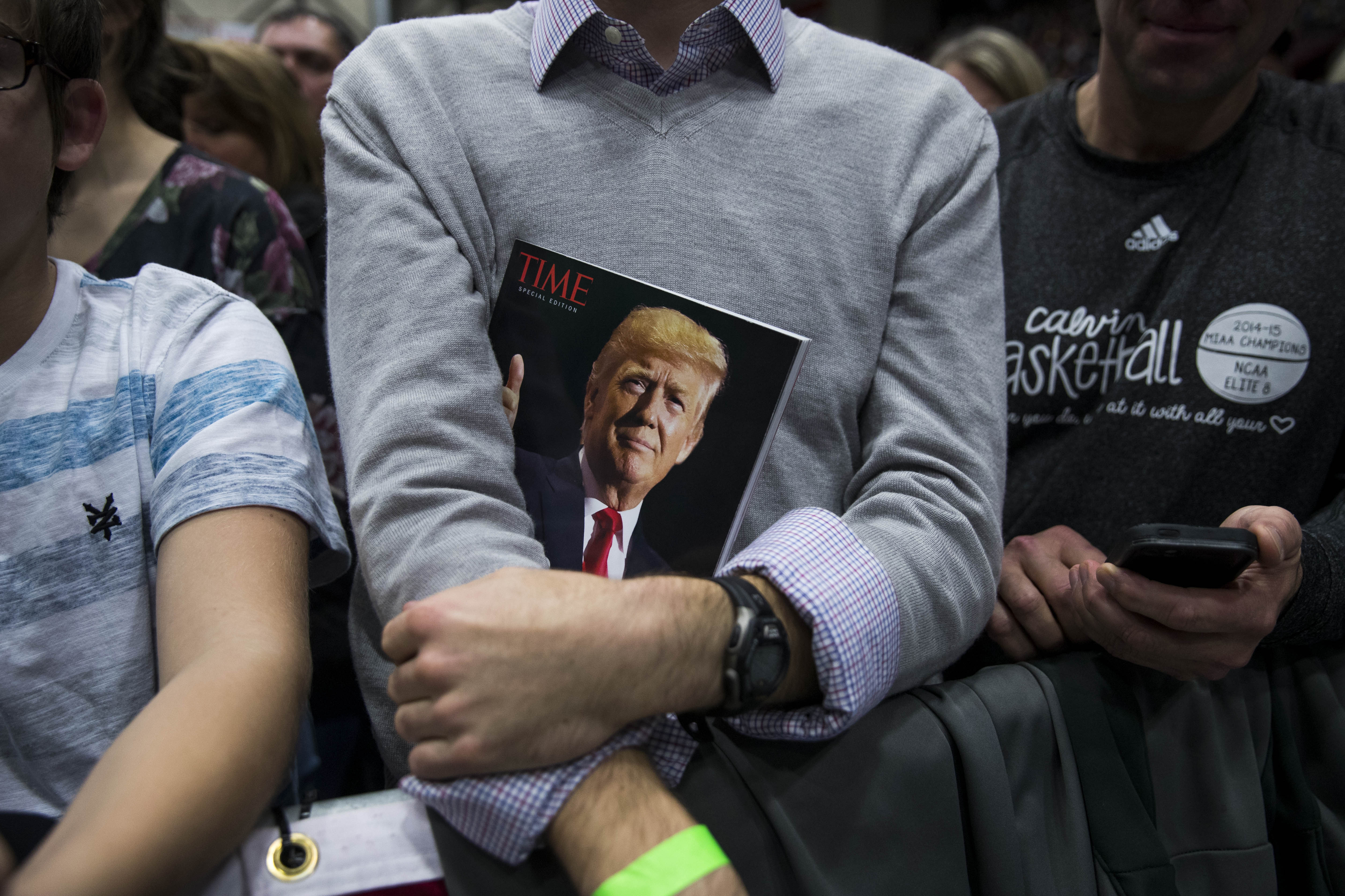 A man holding a copy of Time magazine with President Trump's face on the cover
