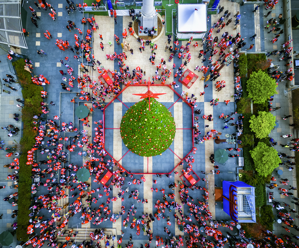 An aerial photo of the giant Macy's Christmas Tree in Union Square, surrounded by Santas.