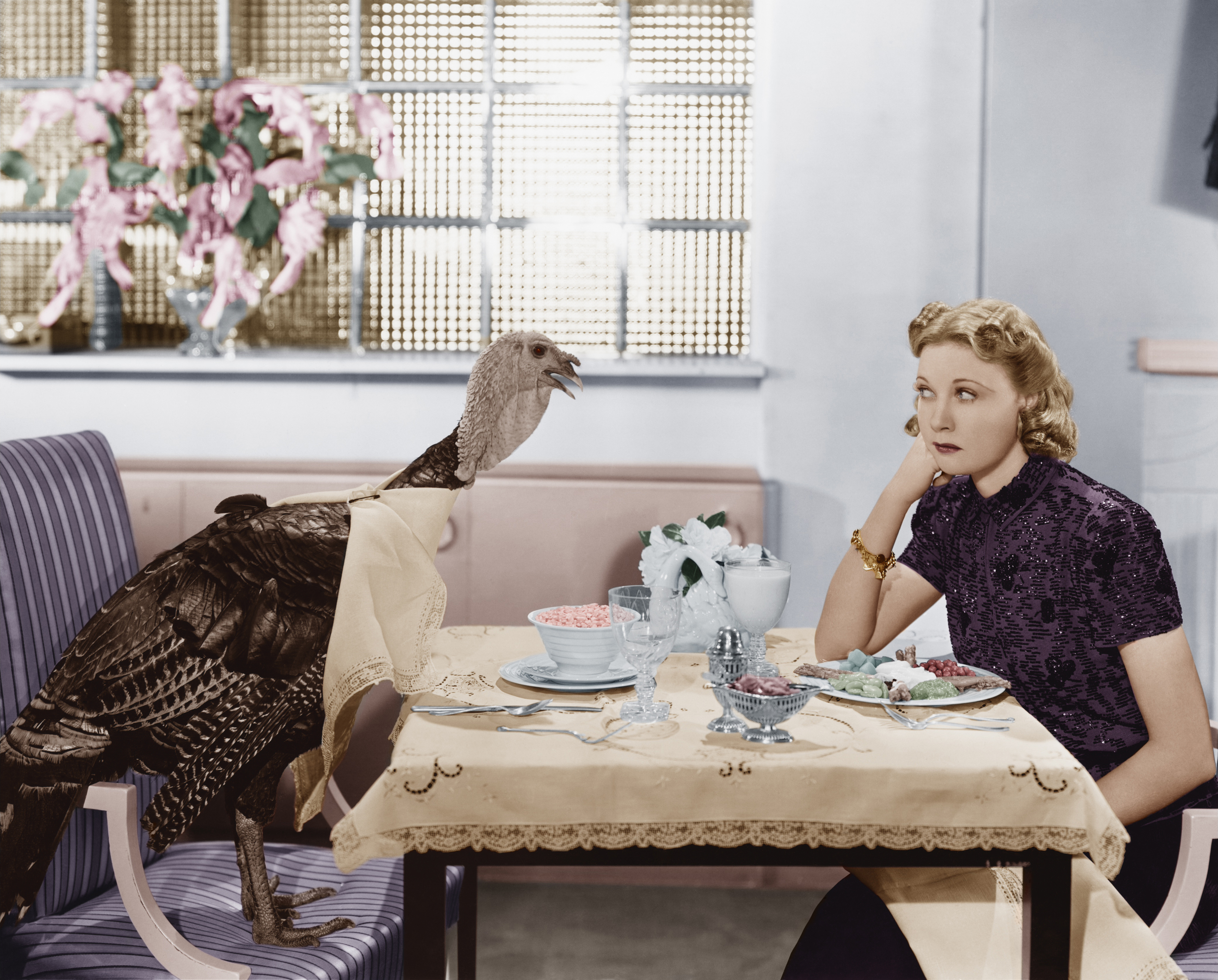 A vintage photo of a woman seated at a dinner table across from a live turkey