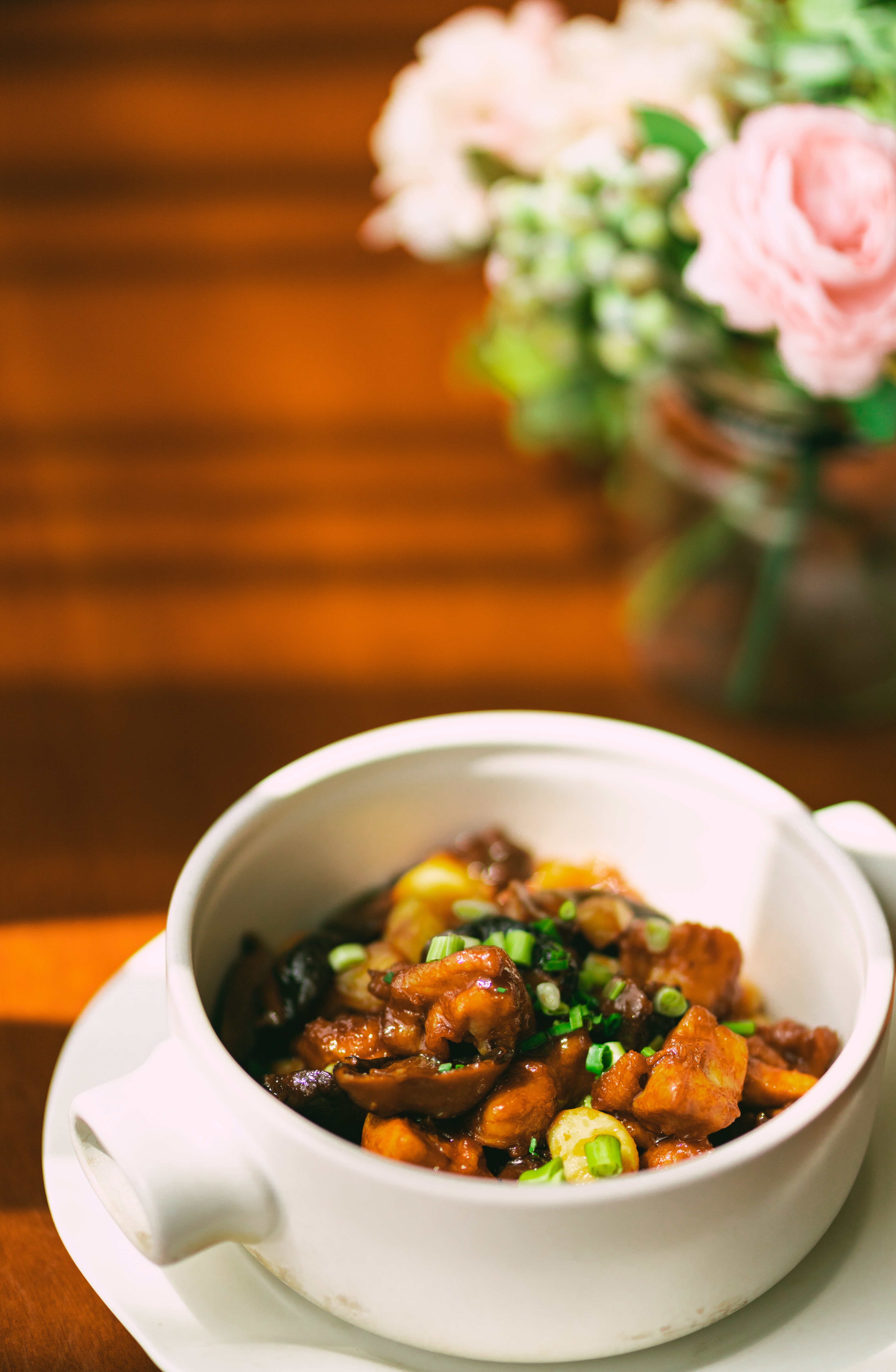 bowl of sweet and sour chicken in a white bowl on a wooden table