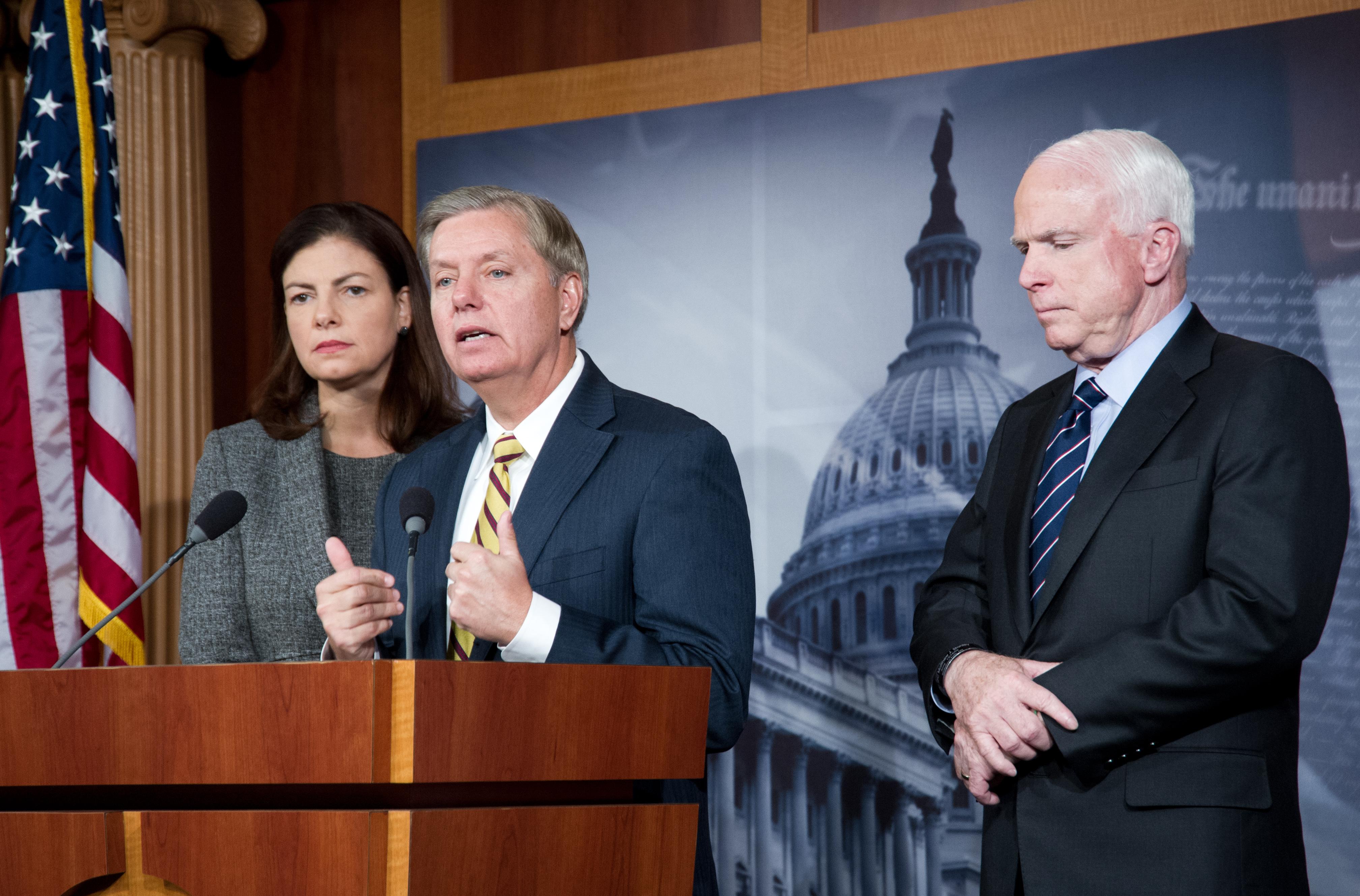 Late US Senator John McCain(R) (R-AZ), Lindsey Graham(c) (R-SC), and Kelly Ayotte (R-NH) during a press conference November 14, 2012 on Capitol Hill in Washington, DC regarding the terrorist attack in Benghazi, Libya on September 11, 2012.