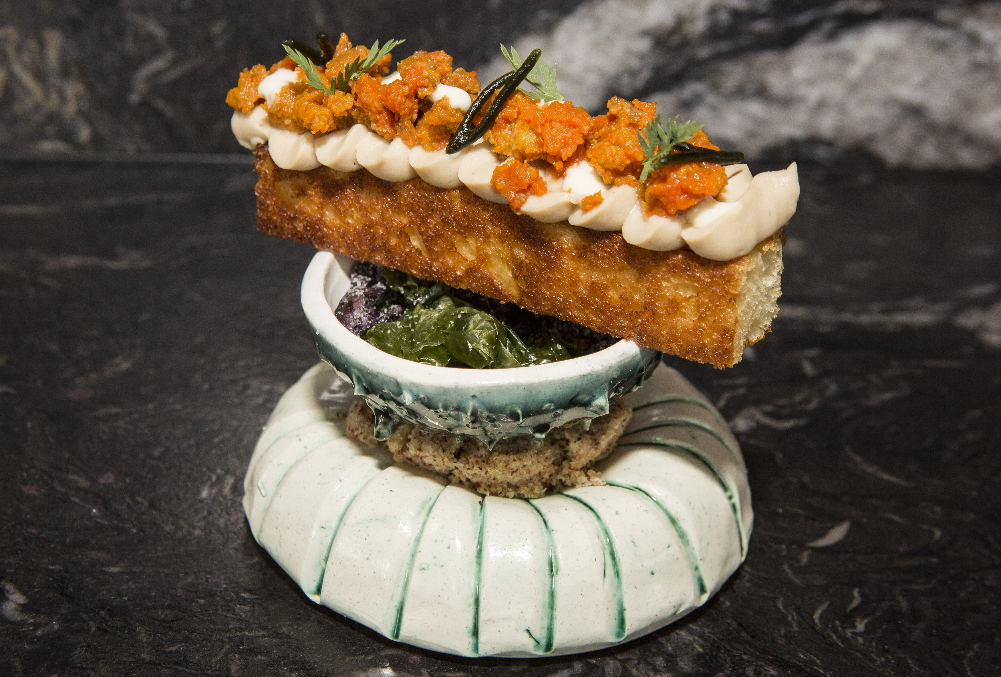 A tall, narrow strip of toast topped with sea urchin