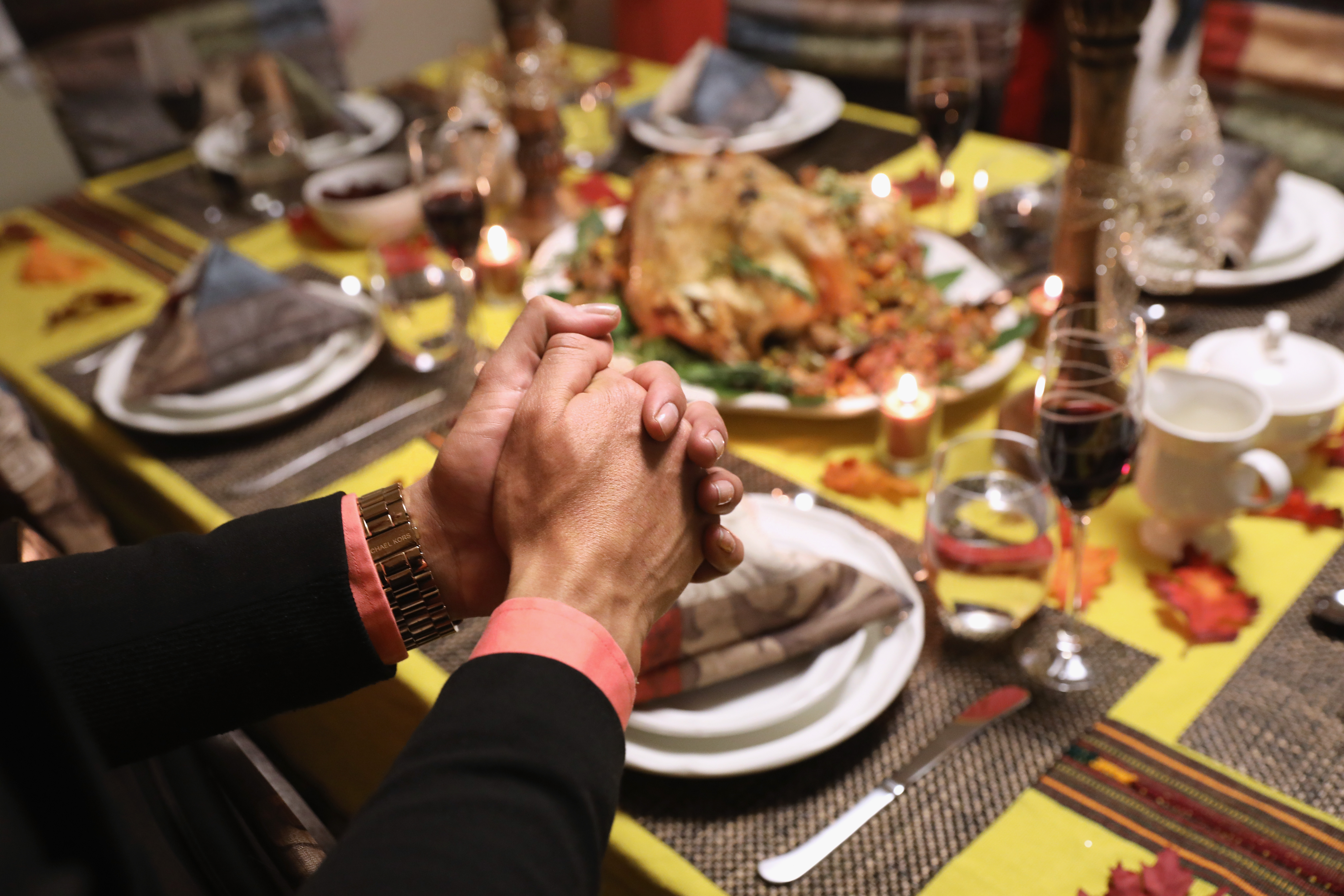 A person sits at a Thanksgiving table with their hands clasped in front of them.