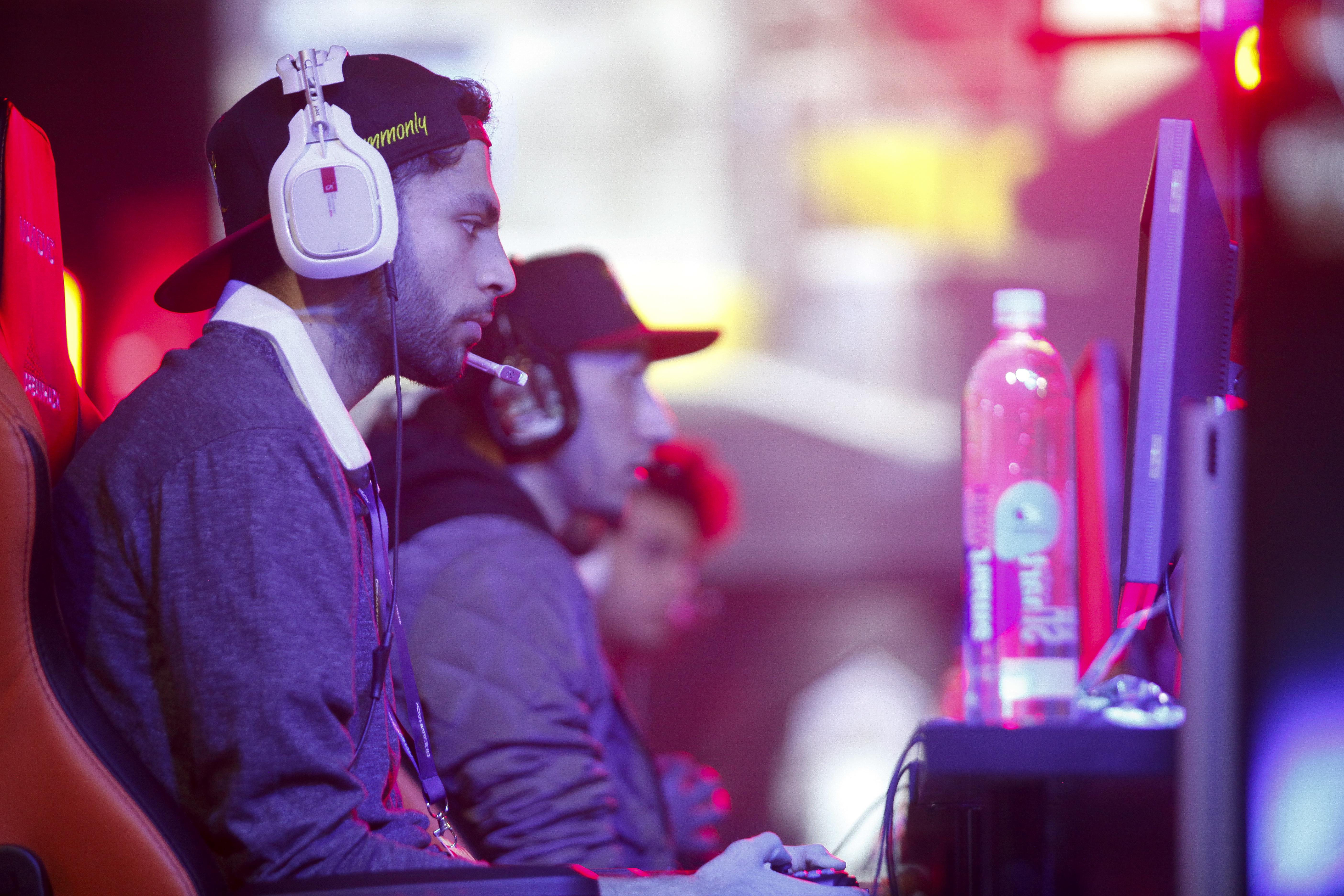 Men in headphones sit and look at gaming screens.