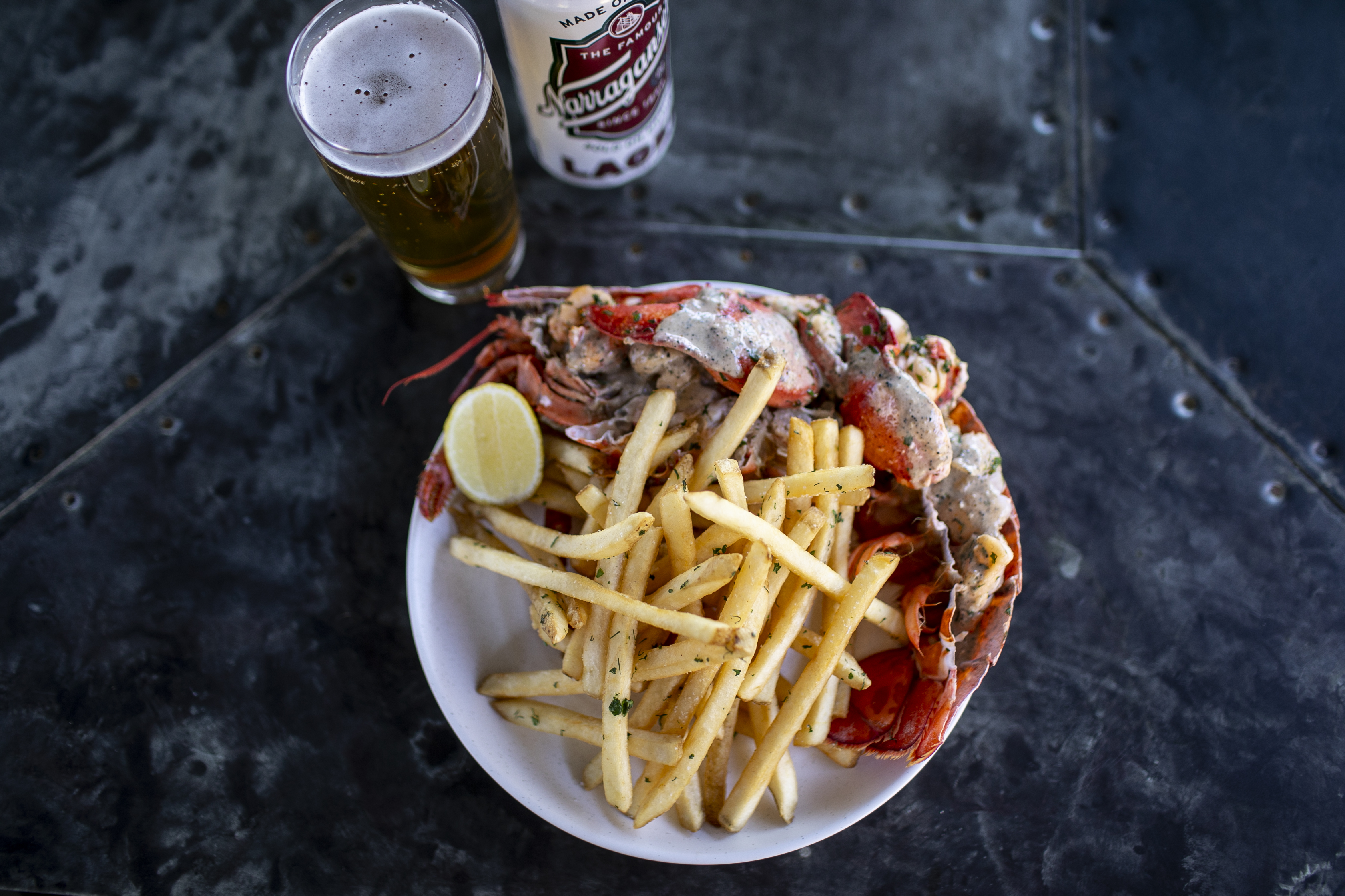 A plate of boiled lobster and fries with a beer