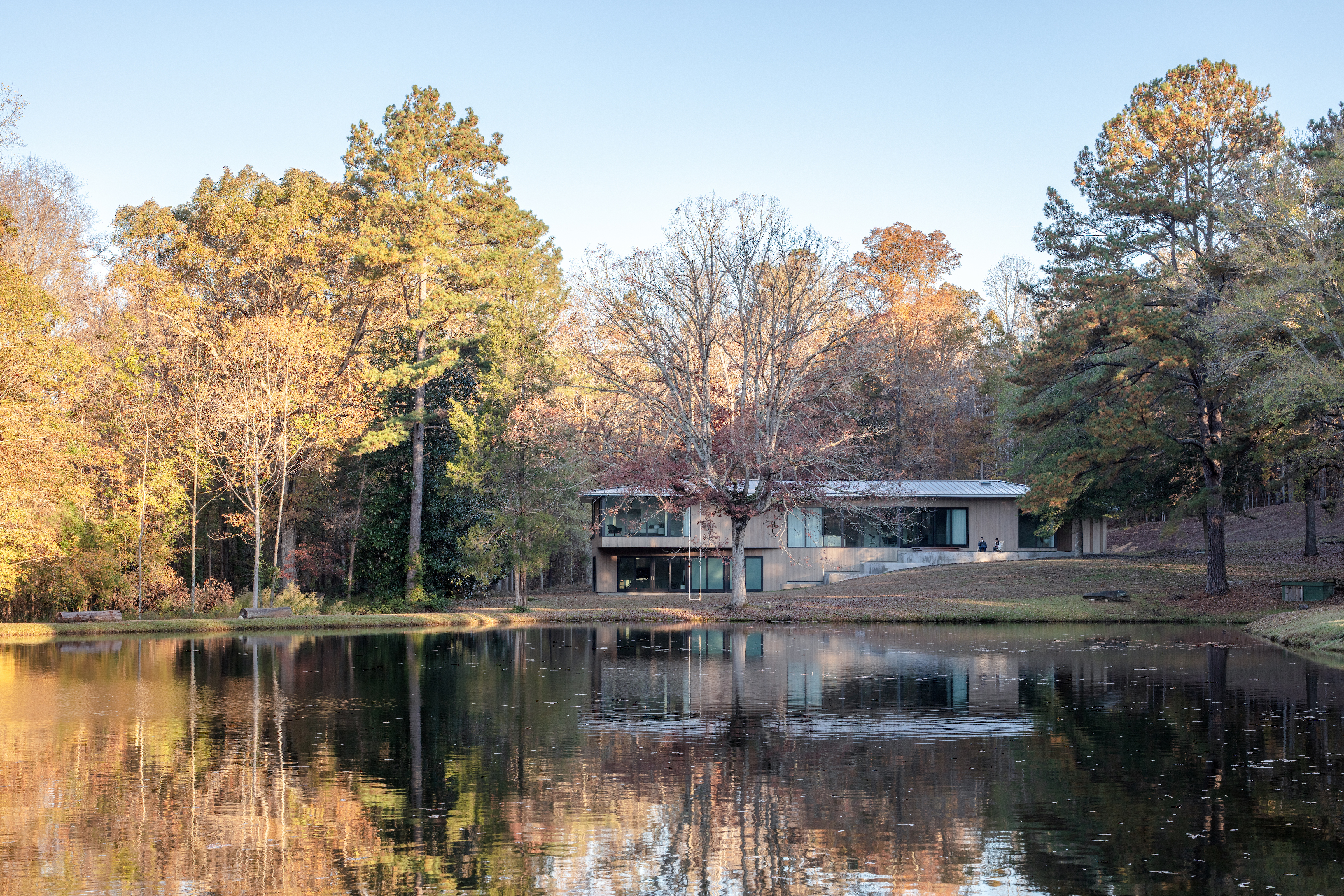The exterior of a house. The house is surrounded by trees and a lake.