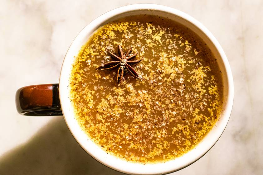 A top shot of a mug of hot buttered cider with a star anise floating on top from Cooks and Soldiers in Atlanta
