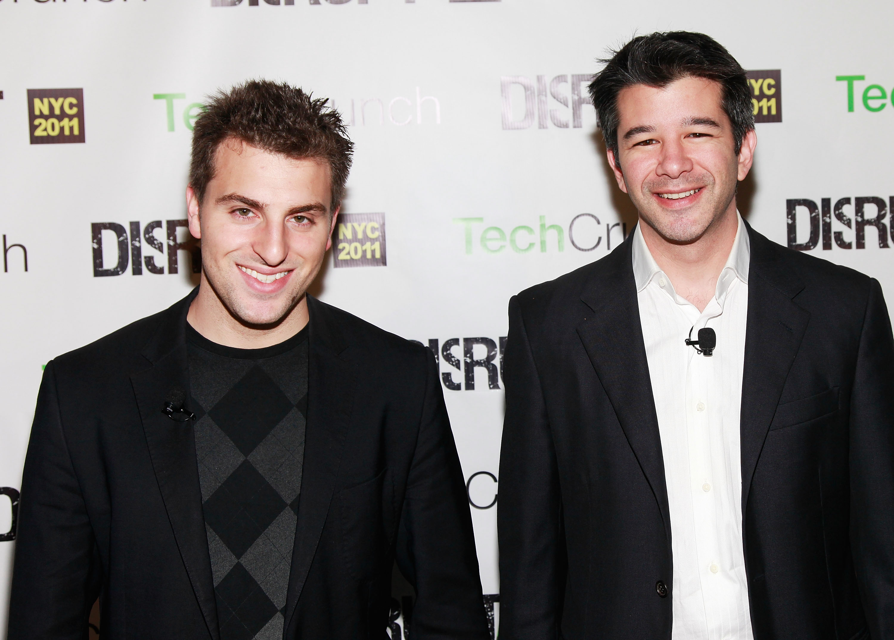 Brian Chesky and Travis Kalanick pose together at TechCrunch Disrupt in New York City in 2011.