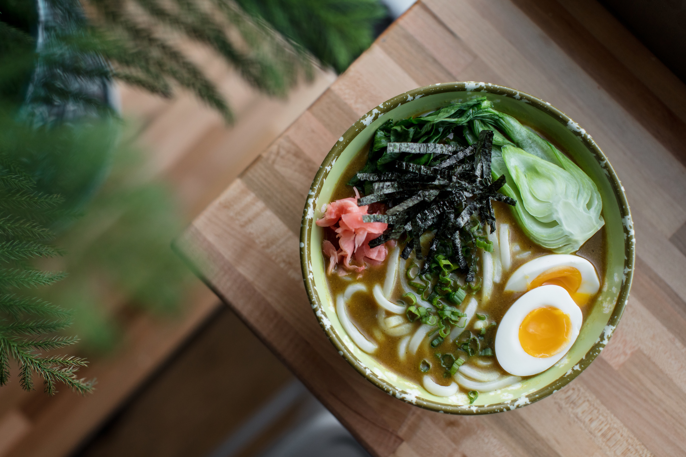 A bowl of udon with eggs, bok choi, nori, and ginger.