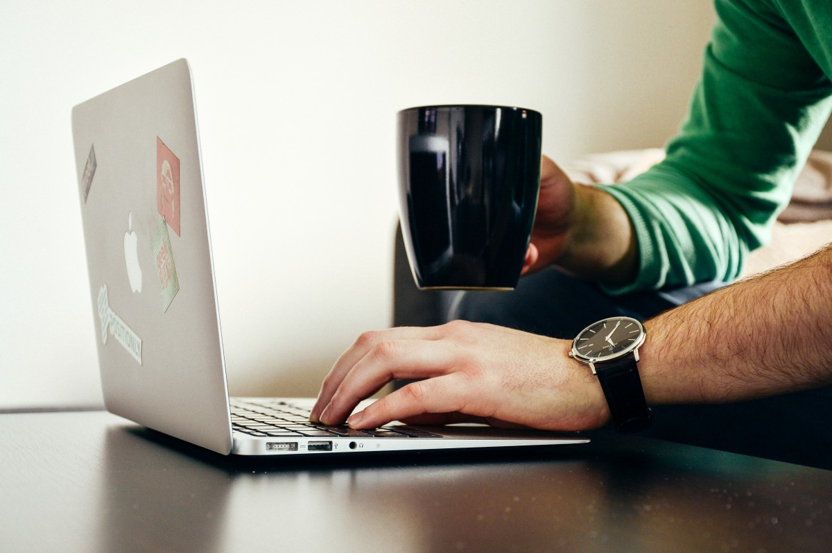 An unidentified person looking at a laptop and holding a cup of coffee