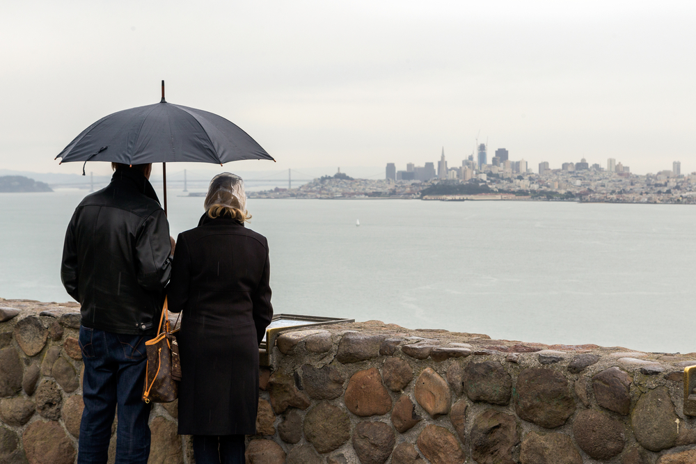 Two people looking at the SF skyline while holding open umbrellas.