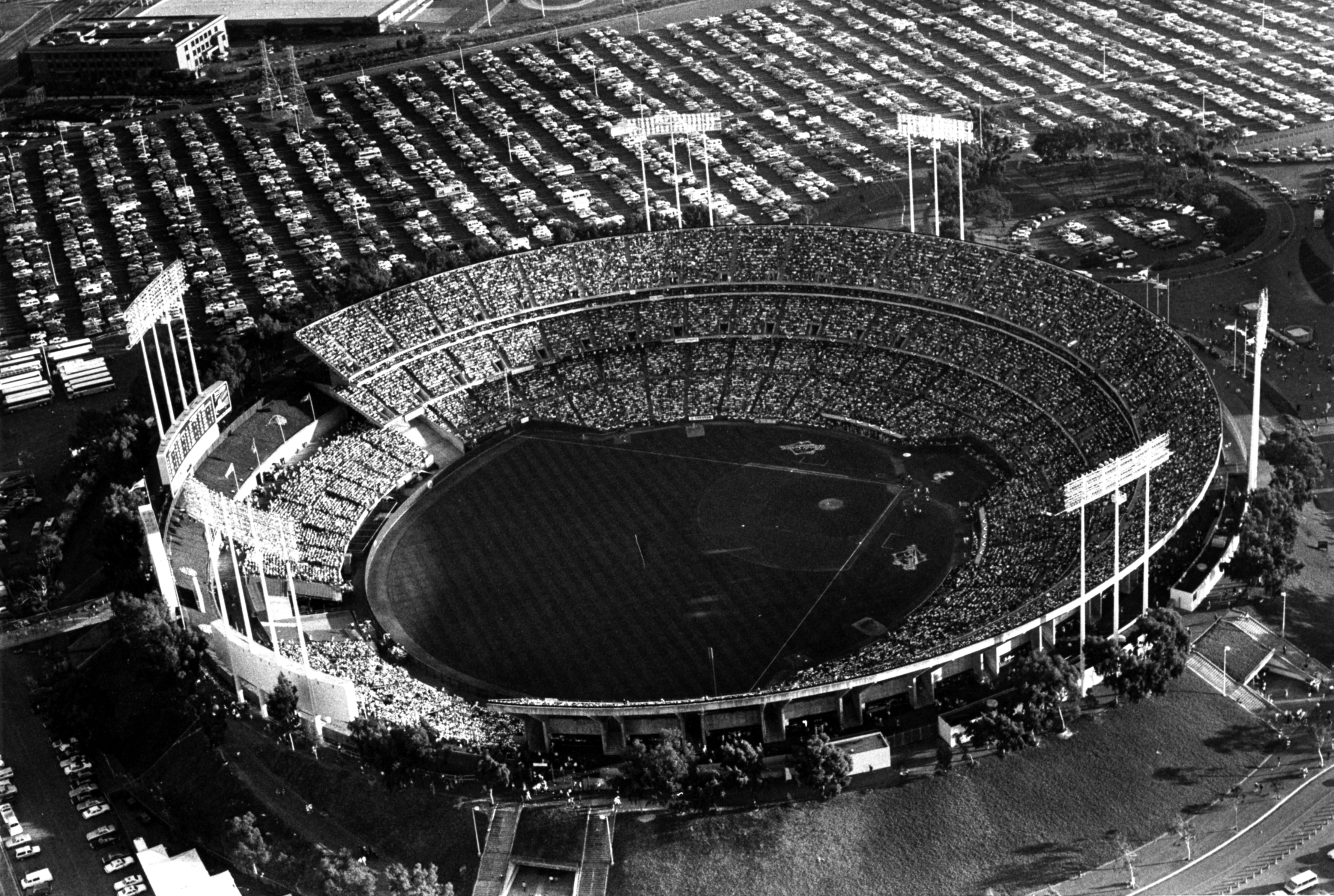 A black and white image of the Oakland Coliseum from above, filled with people. The parking lot in the upper half of the image shows a parking lot filled with cars.