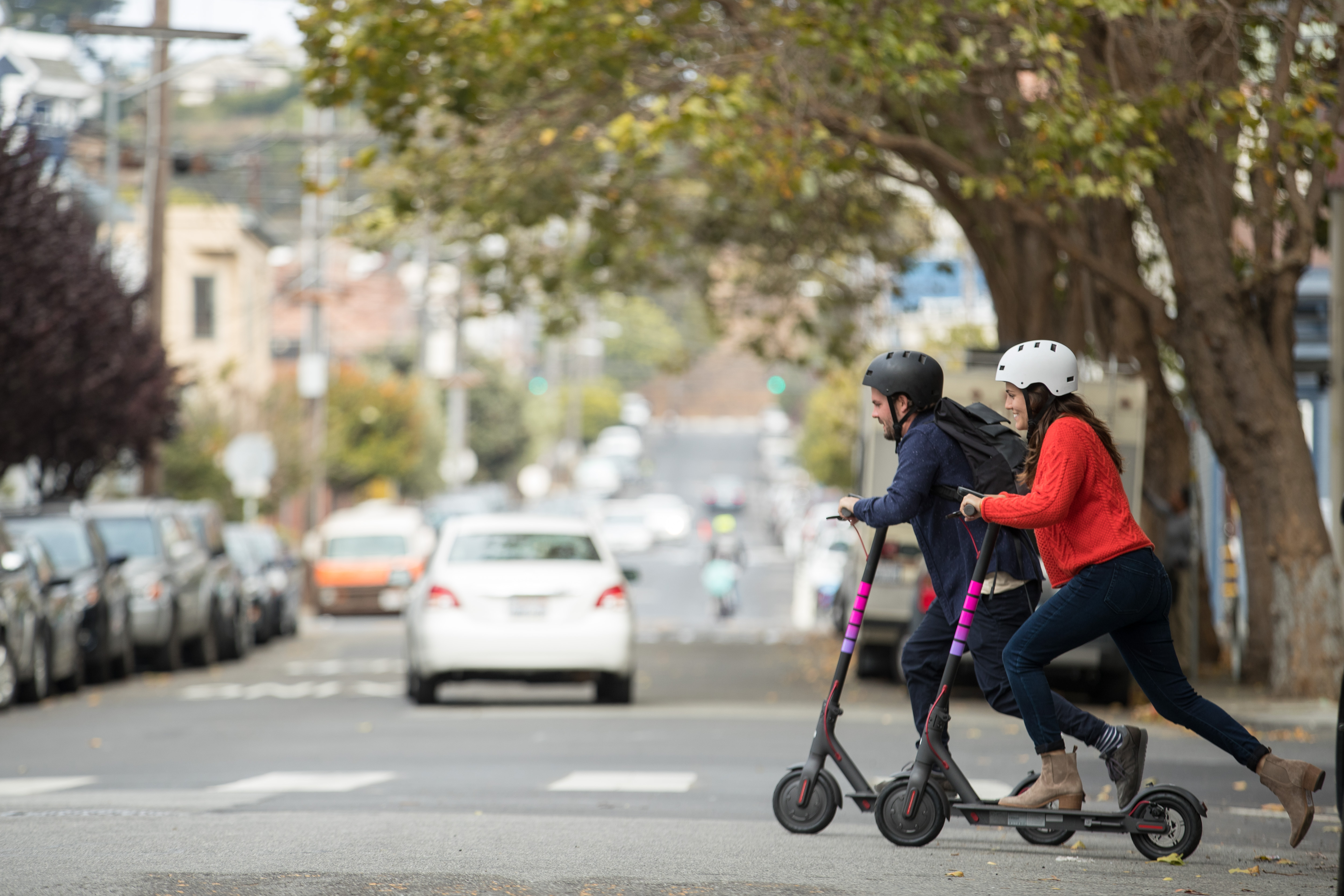 Two riders with helmets using scooters to cross a street