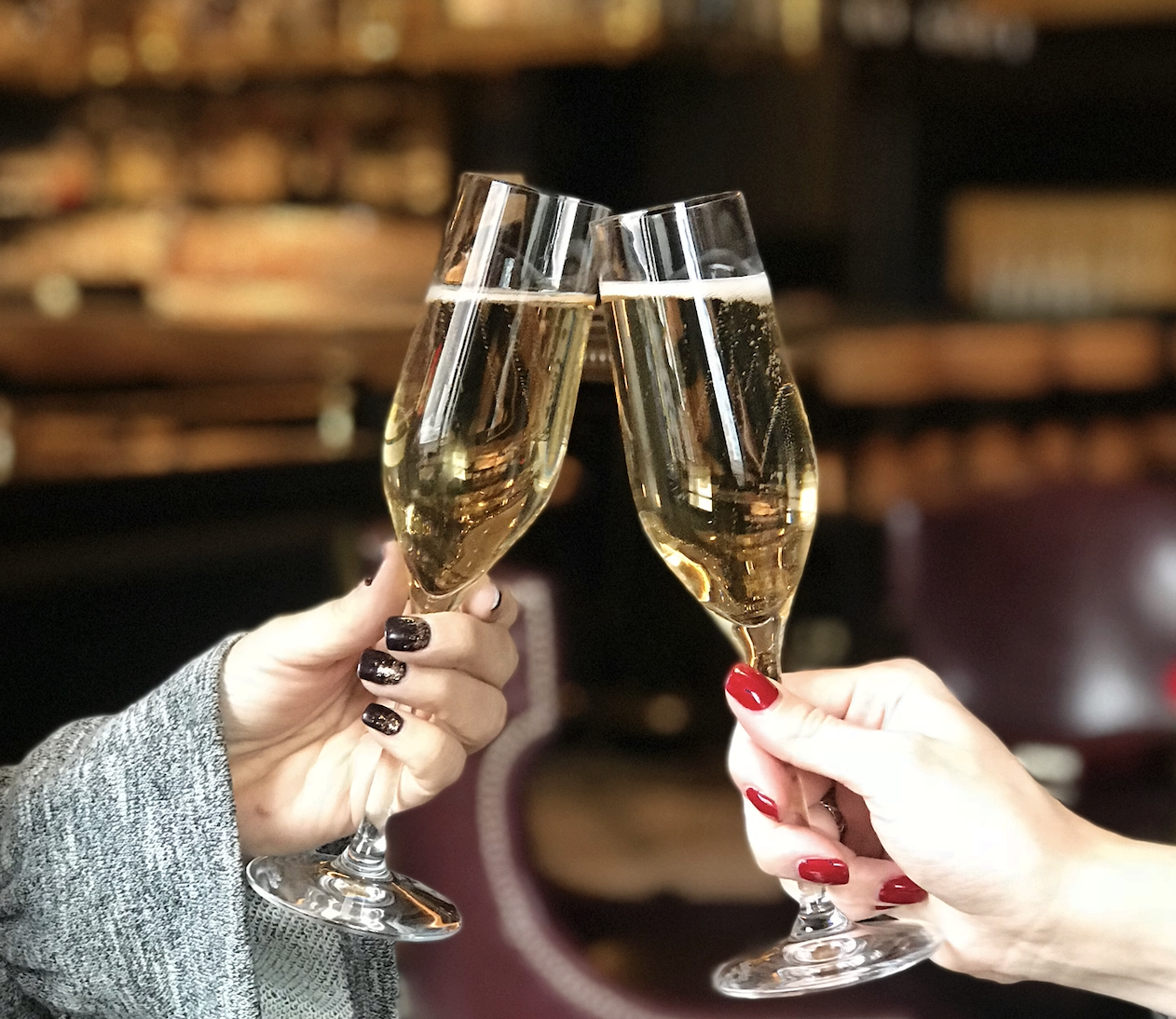 Two hands holding Champagne flutes, cheers-ing.