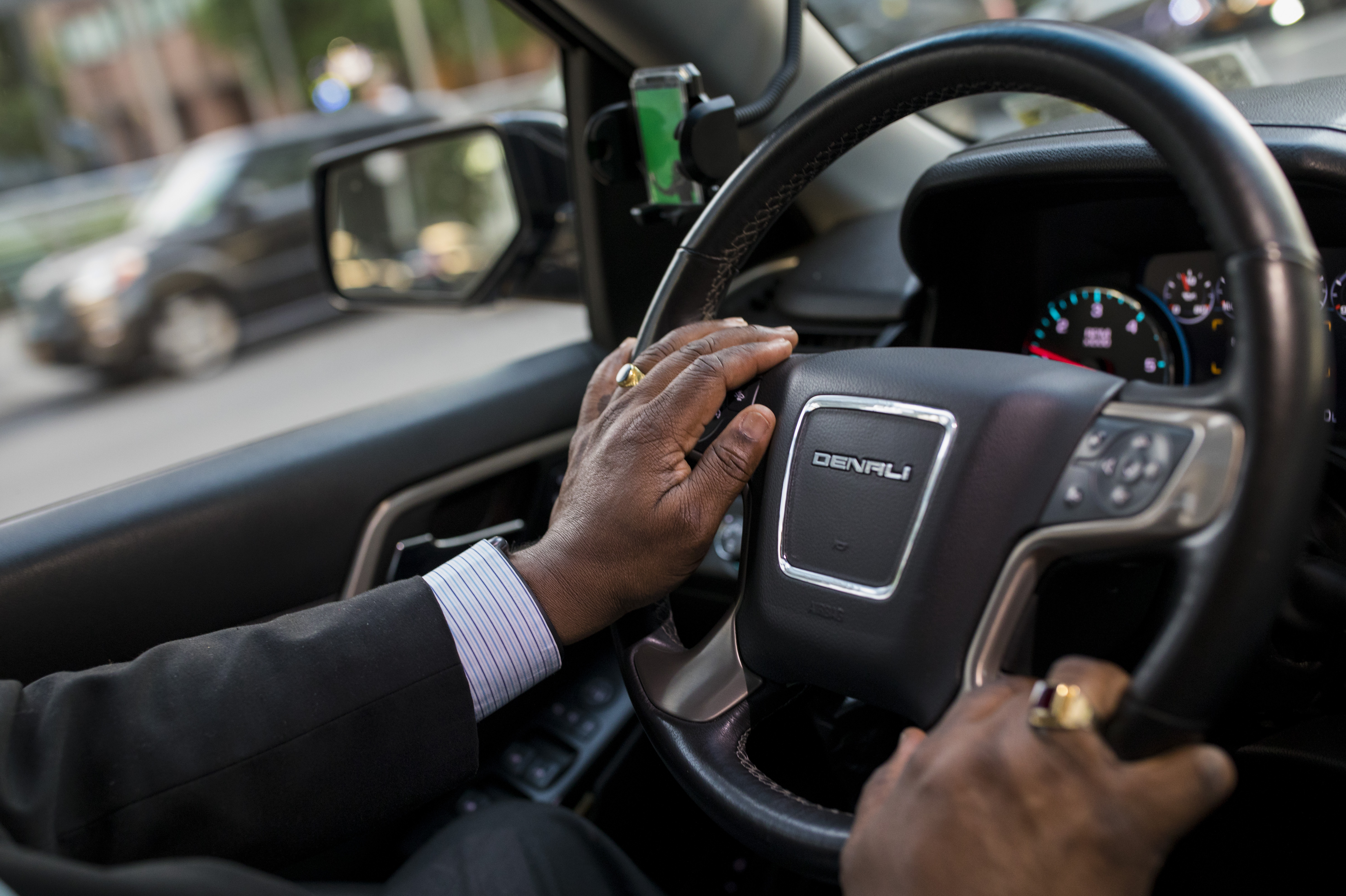 A man's hands on the steering wheel of a car