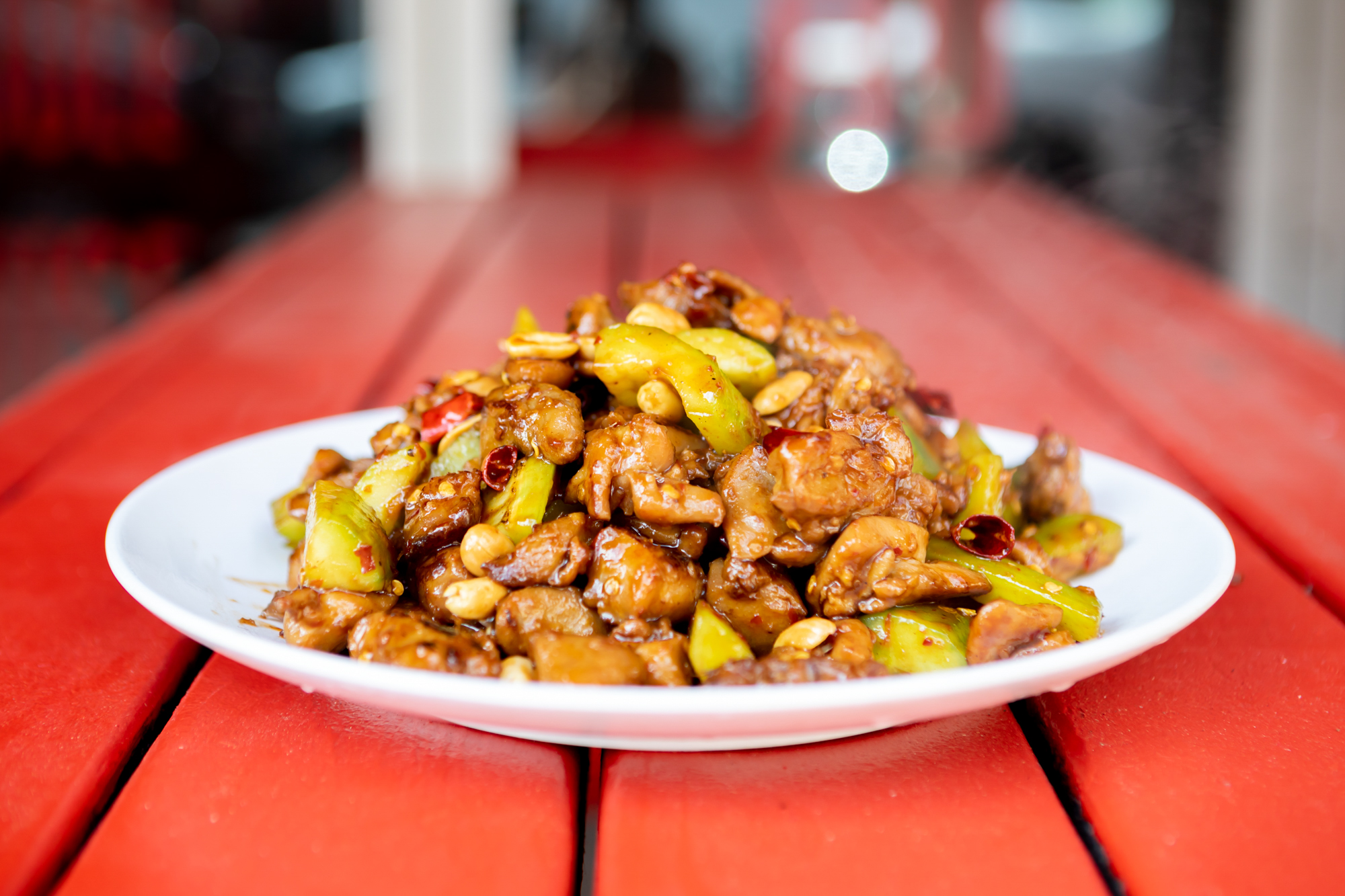 A plate of kung pao chicken on a red table