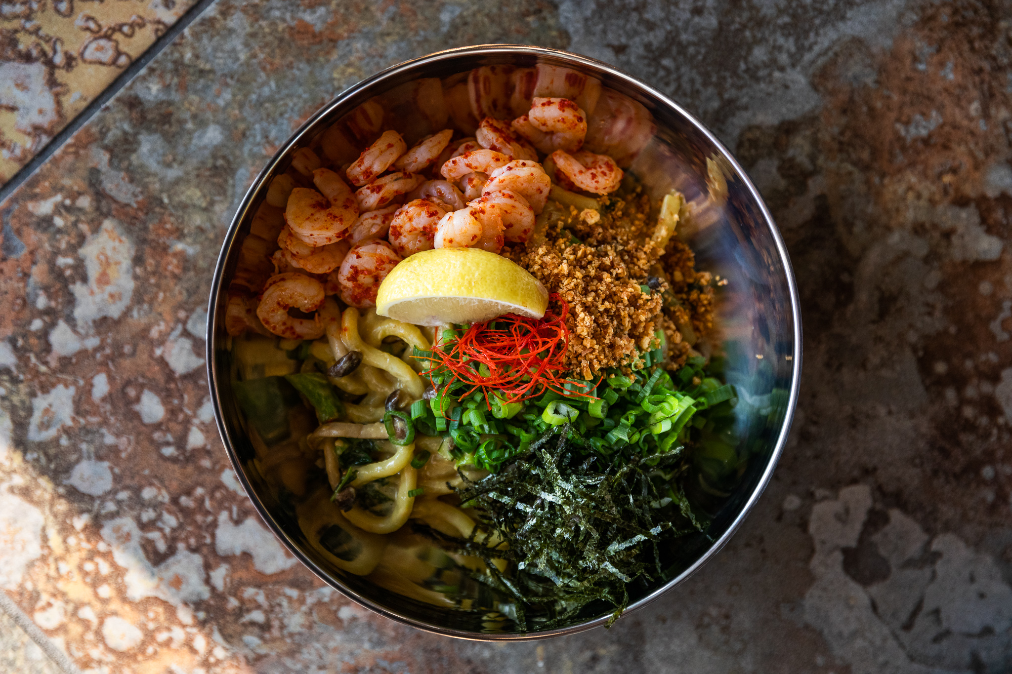 Butter udon noodles with poach shrimp, a lemon wedge, and herbs in a metal bowl.