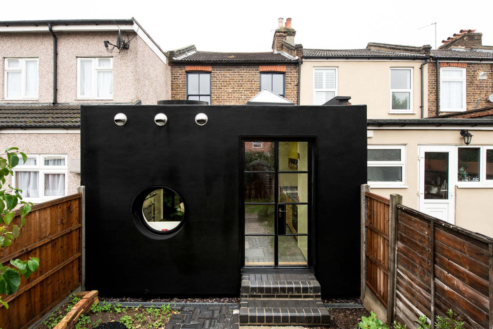 Black cube home in backyard