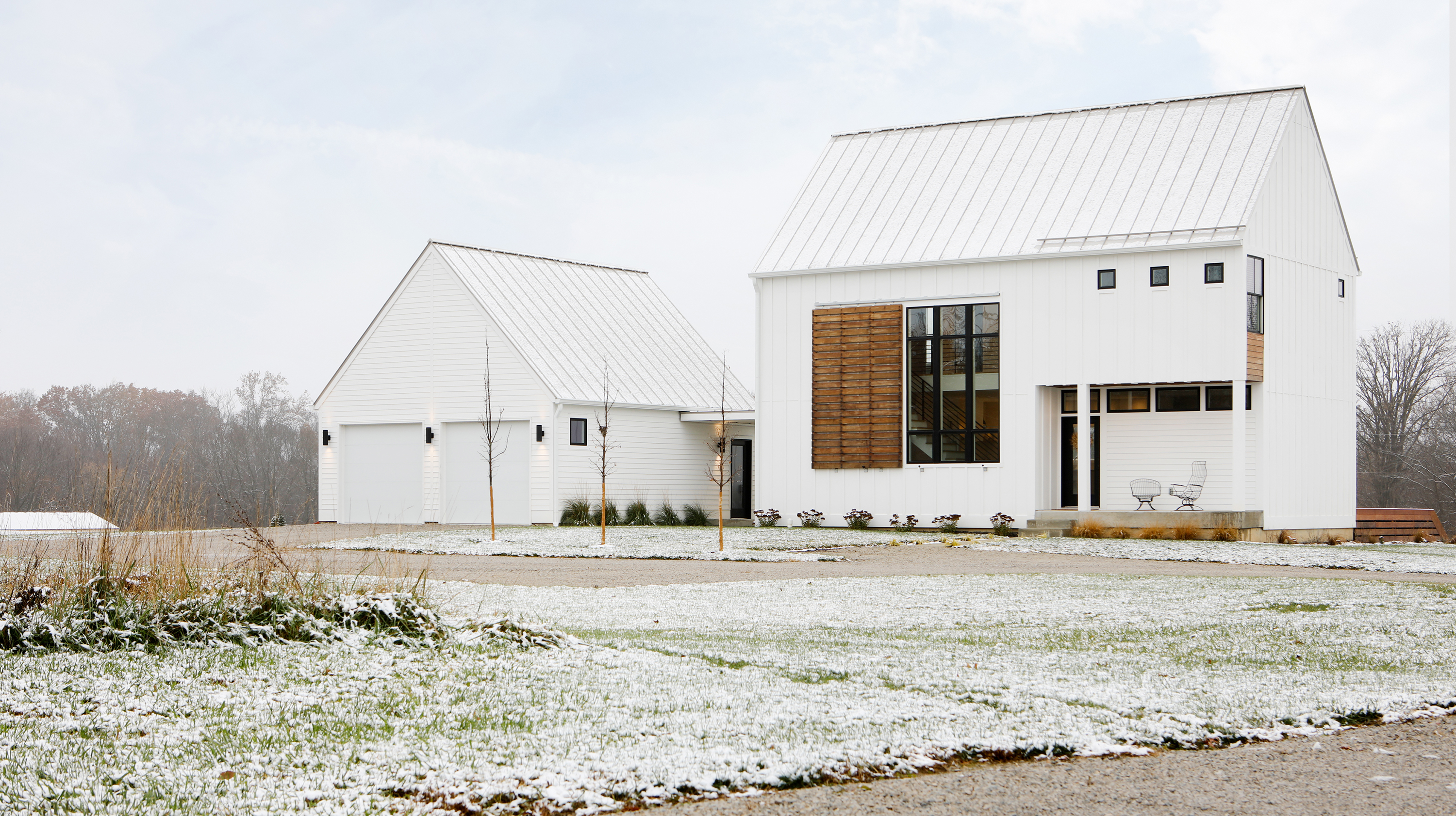 The exterior of two buildings. Both buildings are painted white. In the foreground is a lawn covered in frost and snow.