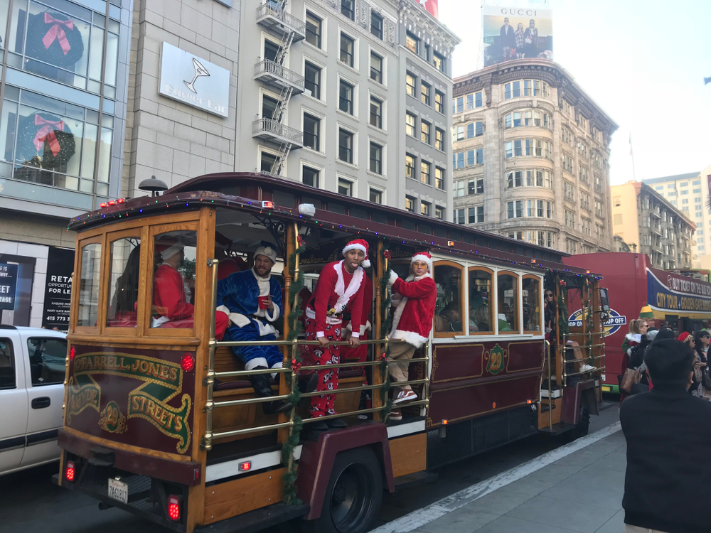 Men in Santa suits hanging out of a Cable Car.