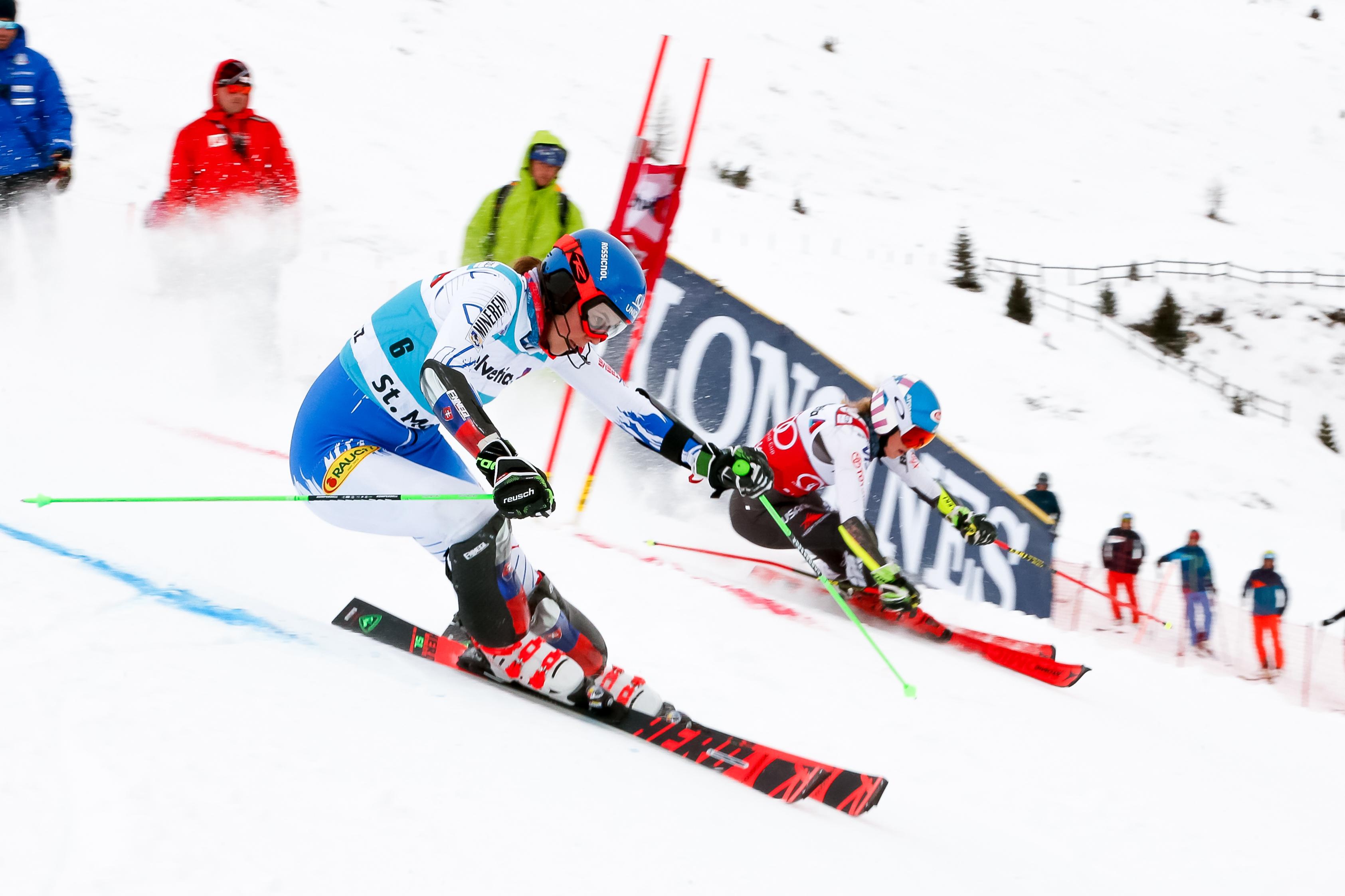 Two skiers racing around slalom gates