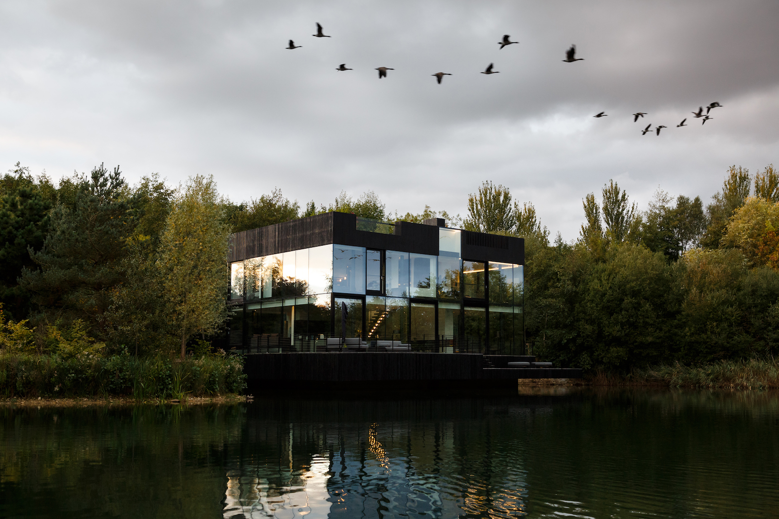 Glass lake house appears to float on water