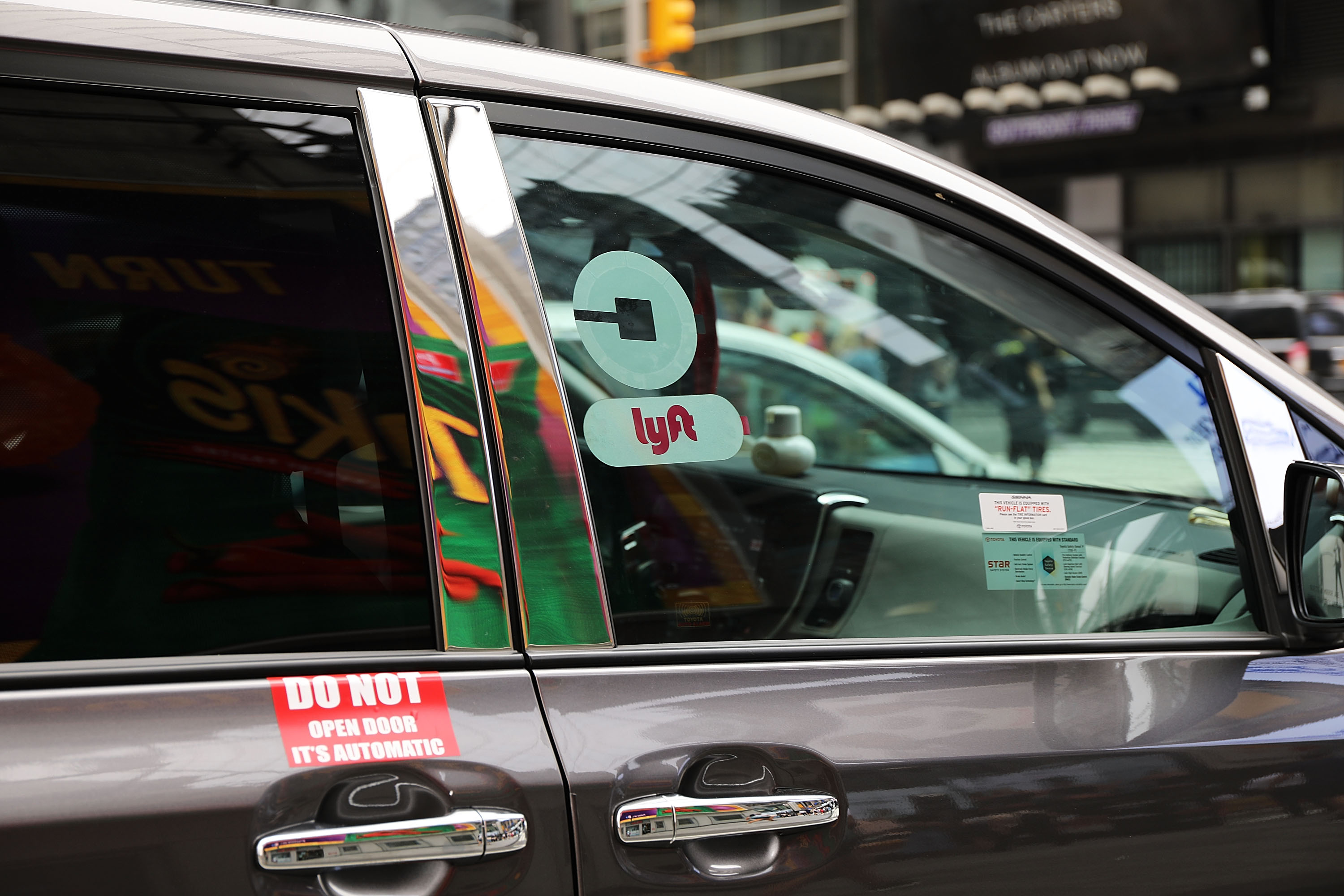 Ride-hailing car in NYC with both Uber and Lyft logos