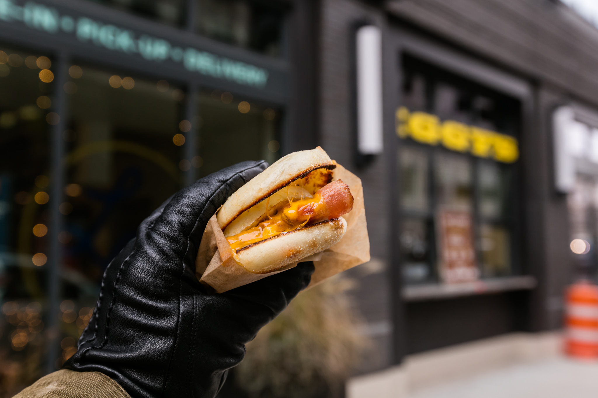 An egg, ham, and cheese breakfast sandwich held in a black-gloved hand.