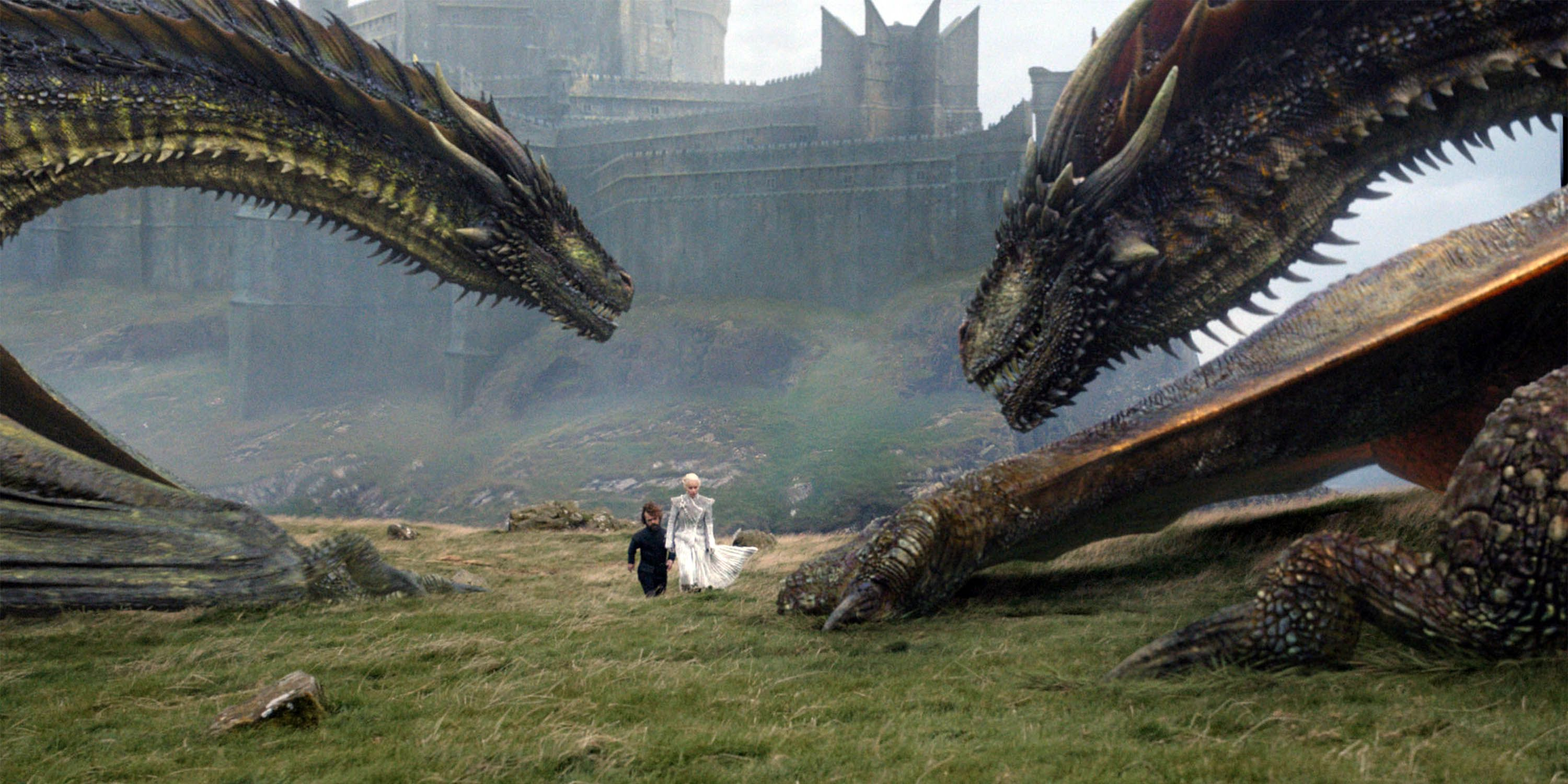 """Two """"Games of Thrones"""" characters walk across a field overlooked by dragons"""