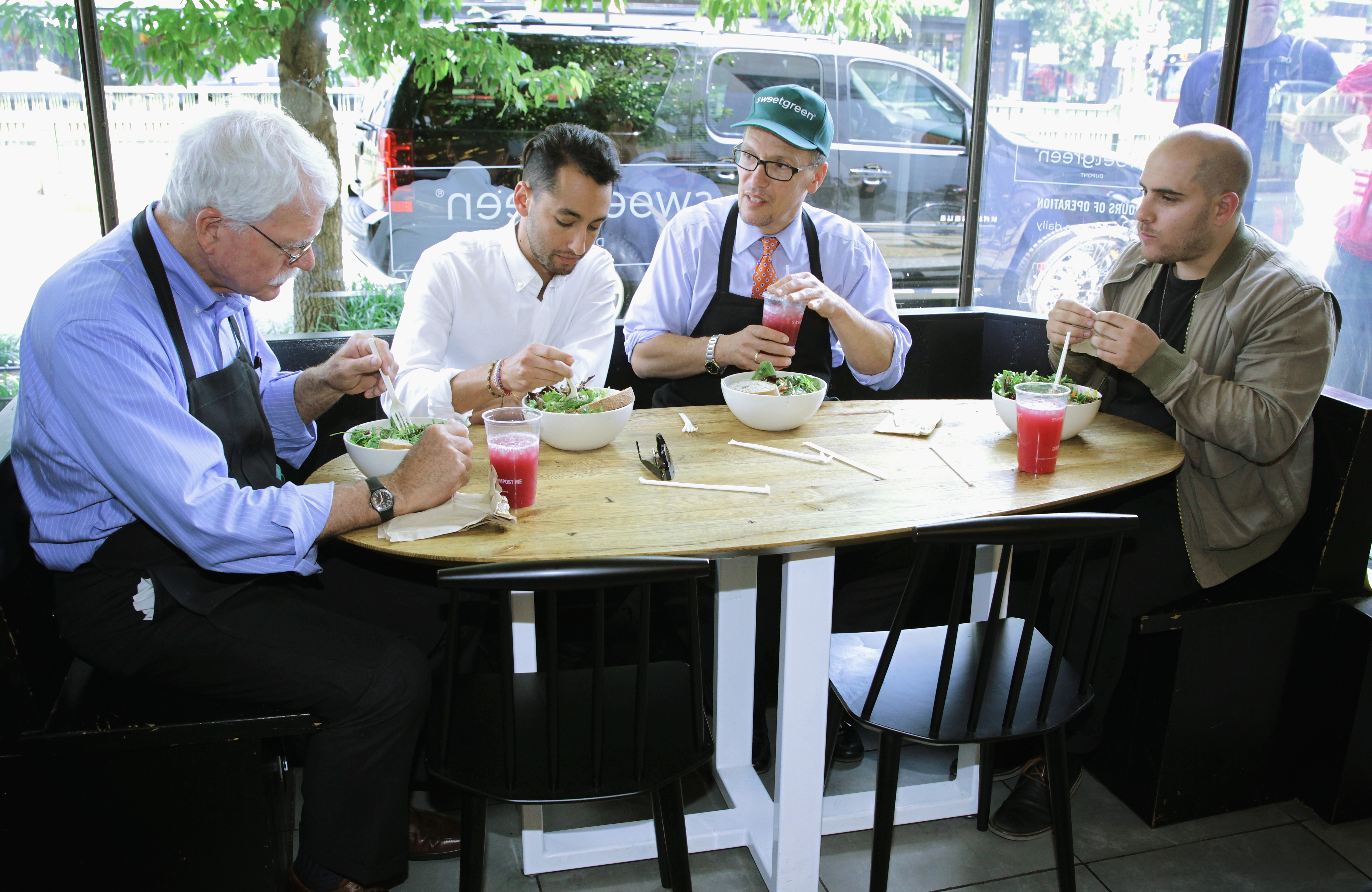 Left to right: Representative George Miller, D-Calif.; Sweetgreen co-founder Jonathan Neman; Labor Secretary Thomas Perez and Sweetgreen co-founder Nicolas Jammet sit at a table in a Sweetgreen restaurant eating salad.