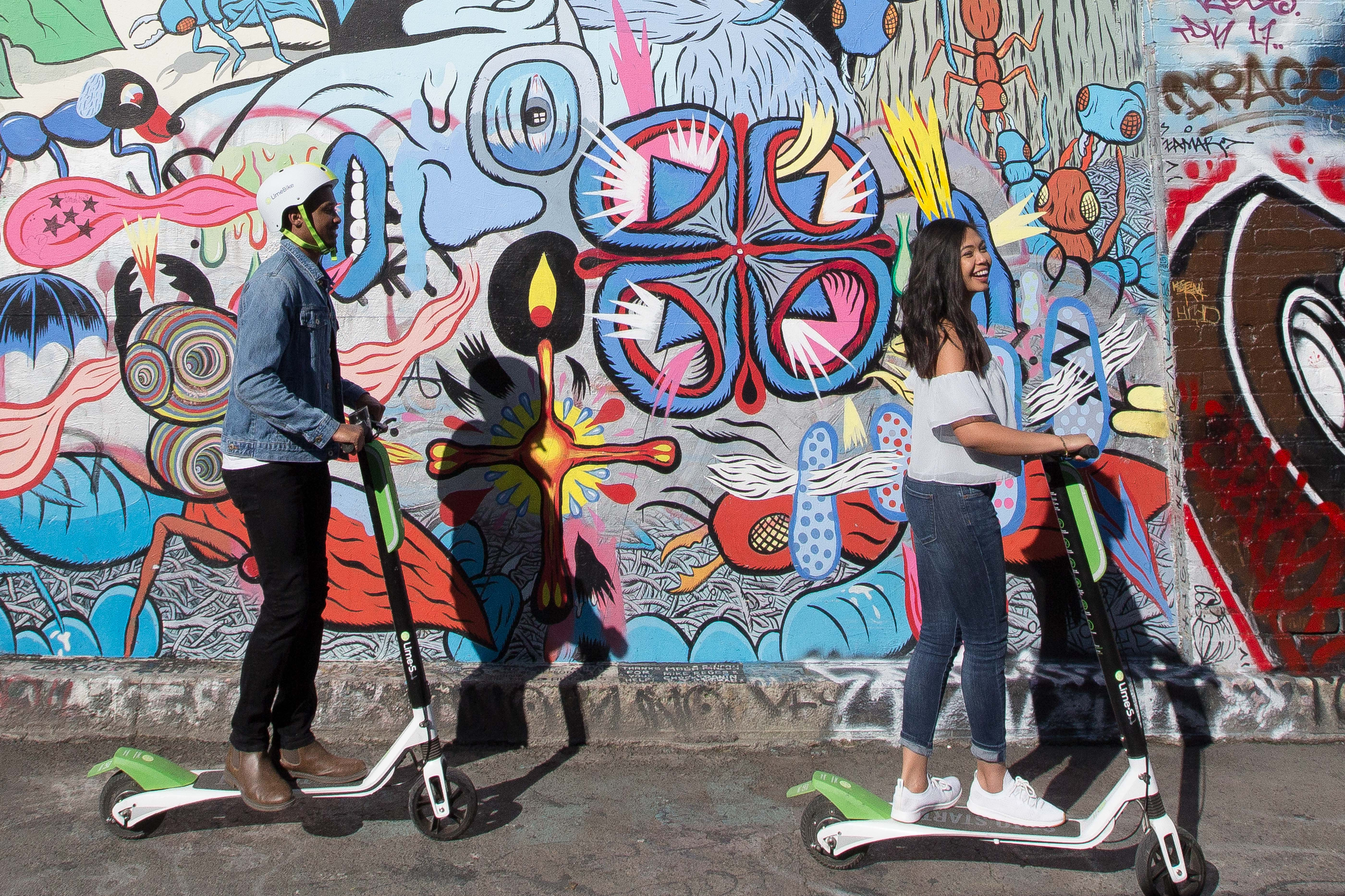 Two people on Lime scooters in front of a colorful mural