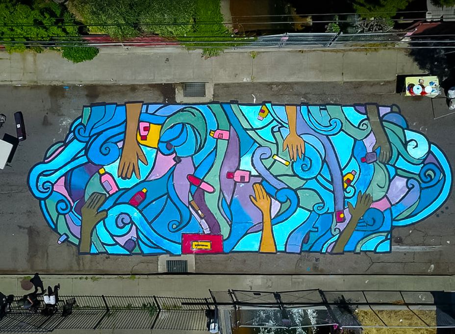An aerial photo of a street mural depicting hands reaching across a field of frenzied blue lines.