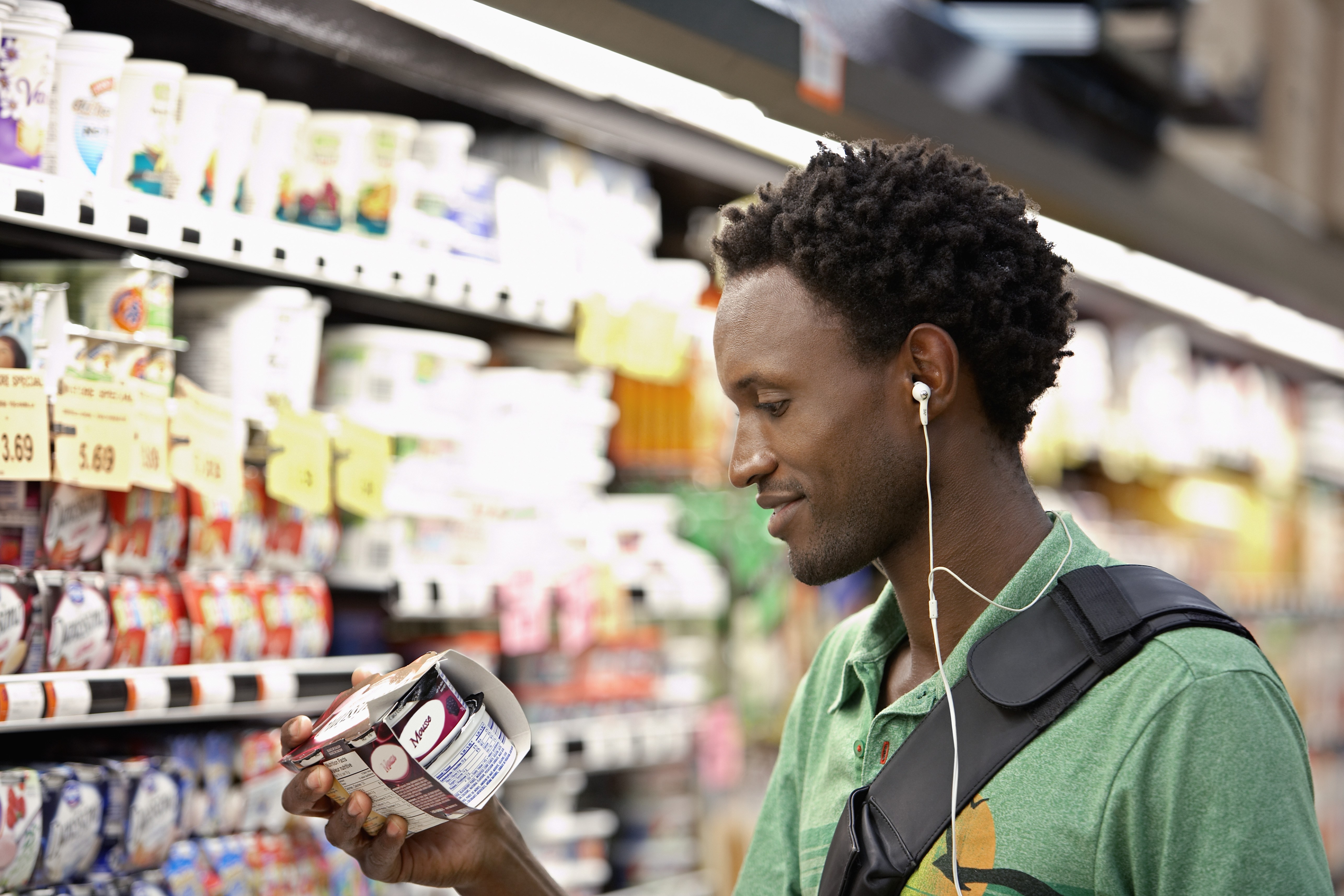 A shopper looks at a yogurt package in a grocery store aisle.