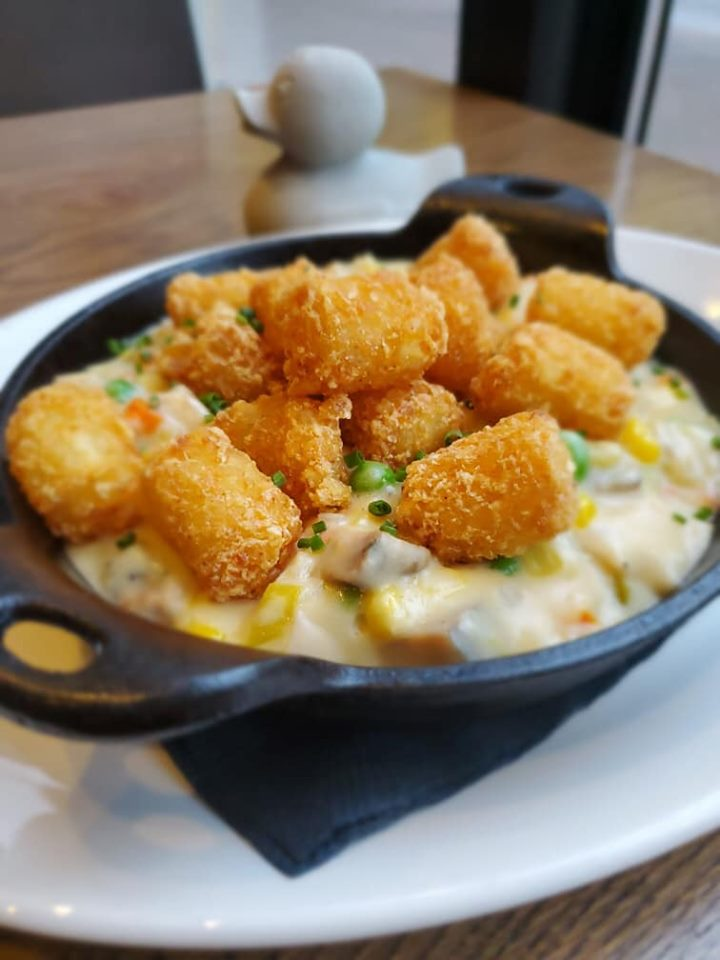 A small cast iron pan holds something creamy with visible peas, topped with tater tots