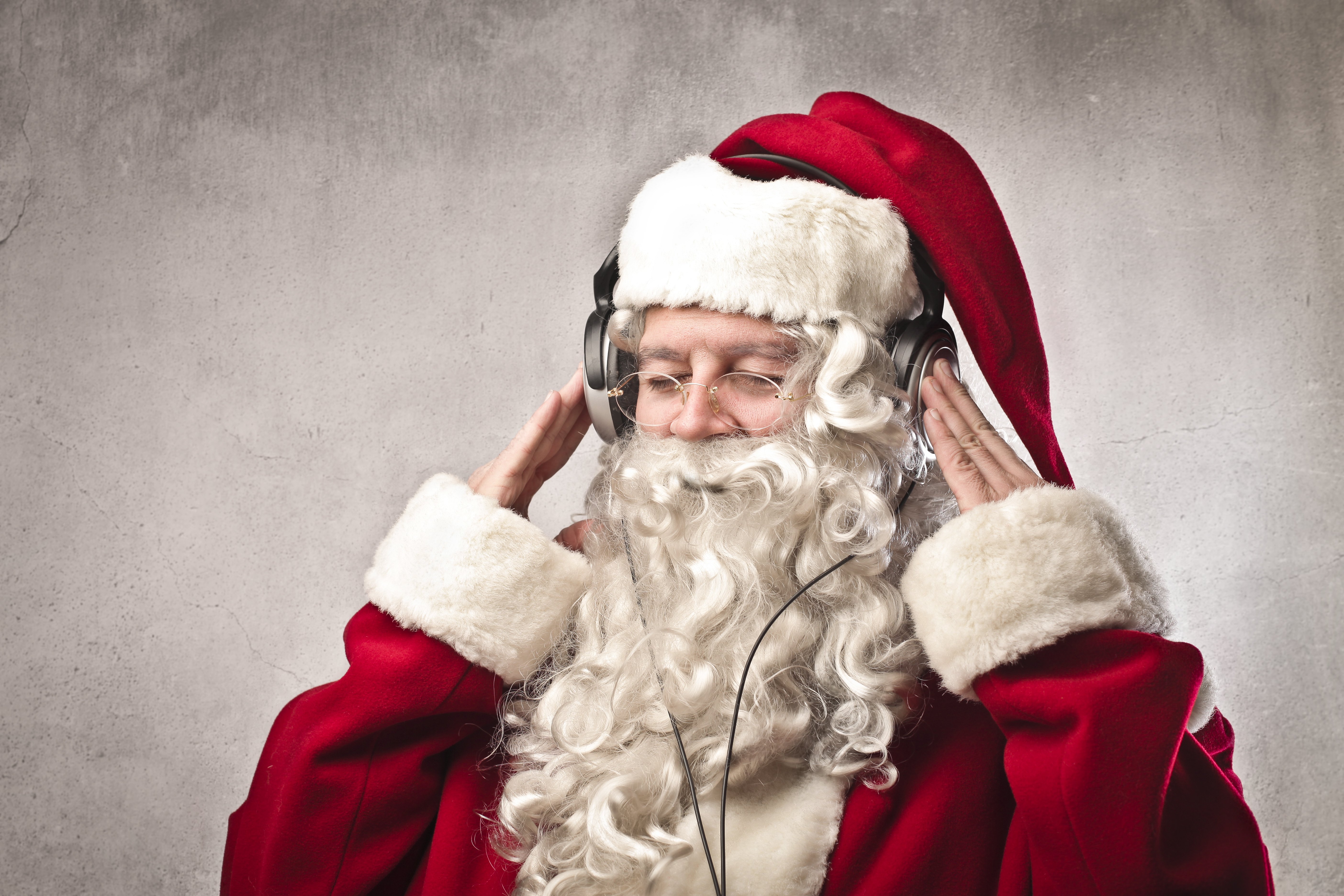 A person dressed in a Santa costume and wearing over-ear headphones.