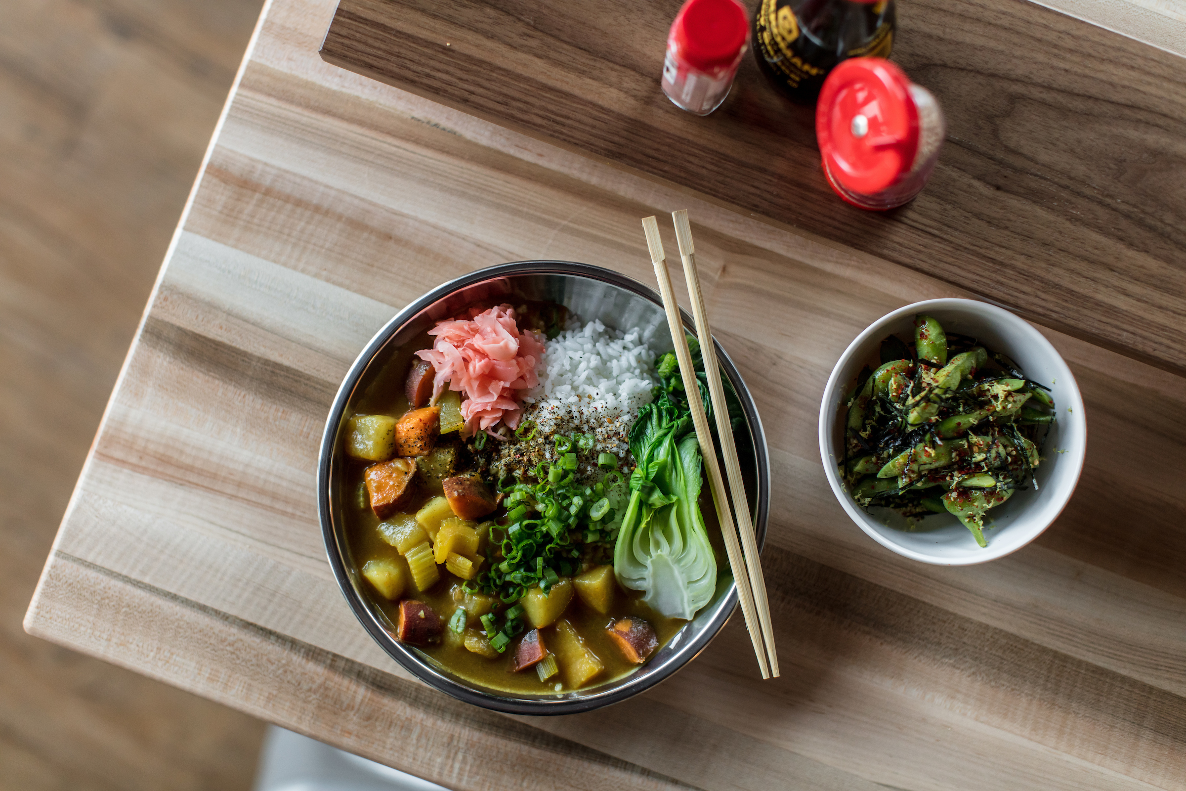 A bowl of golden curry and rice with bok choy and veggies with a side of edamame.